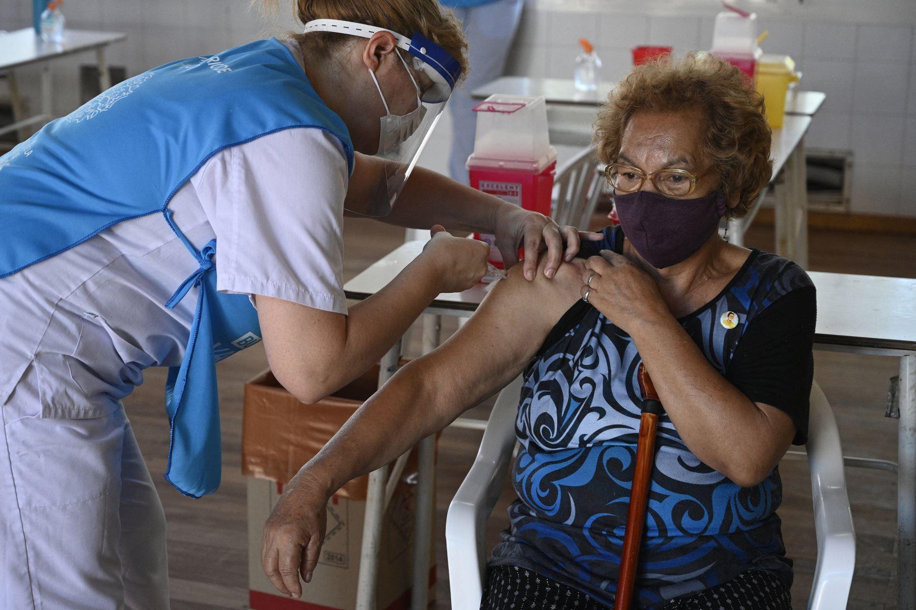 Un trabajador de salud aplica una dosis de la vacuna Sputnik V contra Covid-19, a una anciana en un centro de vacunación temporal en una escuela pública en Ezeiza, en las afueras de Buenos Aires, el 18 de febrero de 2021. Foto: AFP