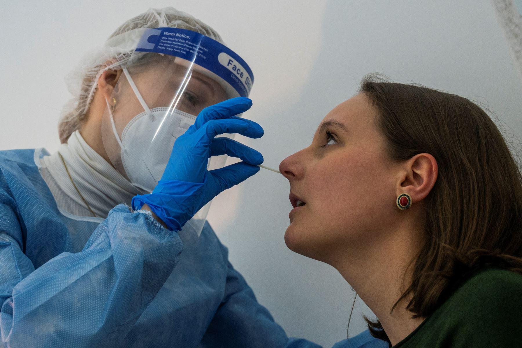 Un profesional de la salud toma una muestra de un paciente con un hisopo para una prueba rápida de antígeno Covid-19 en un centro especializado de Berlín el 17 de febrero de 2021. Foto: AFP