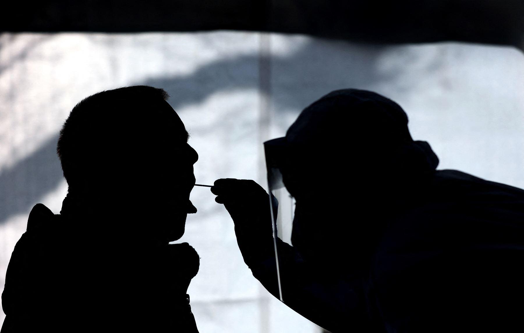 Un trabajador de la salud examina a una persona en un centro gratuito de pruebas rápidas Covid-19 el 3 de febrero de 2021, en Naumburg, Alemania oriental. Foto: AFP