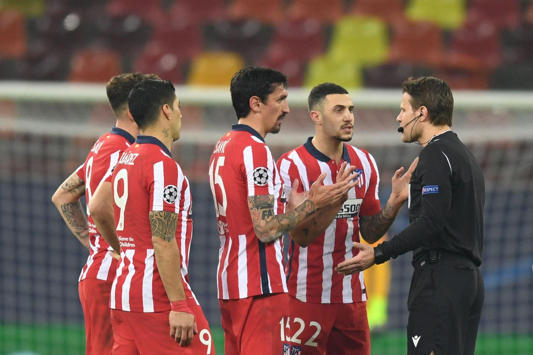 Los jugadores del Atlético de Madrid hablan con el árbitro alemán Felix Brych durante el partido de ida de los octavos de final de la Liga de Campeones de la UEFA entre el Club Atlético de Madrid y el Chelsea. Foto AFP