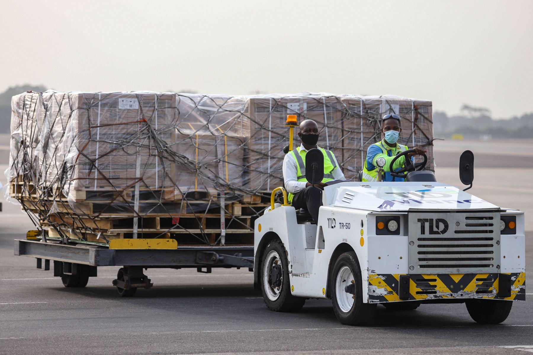 Los trabajadores transportan un lote de vacunas AstraZeneca/ Oxford contra la Covid-19 adquiridas por Ghana a través del mecanismo COVAX, en el Aeropuerto Internacional de Kotoka en Accra, el 24 de febrero de 2021. Foto: AFP