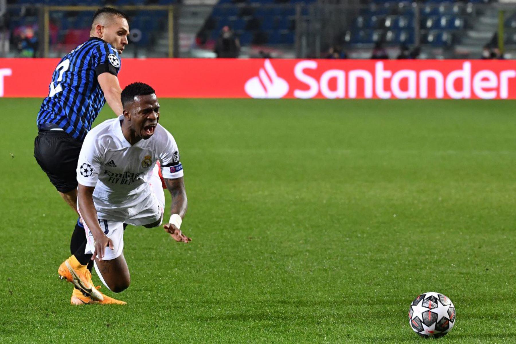 El defensor brasileño del Atalanta Rafael Toloi (L) aborda al delantero brasileño del Real Madrid Vinicius Junior durante los octavos de final de la Liga de Campeones de la UEFA el primer partido de fútbol Atalanta vs Real Madrid  Foto:AFP