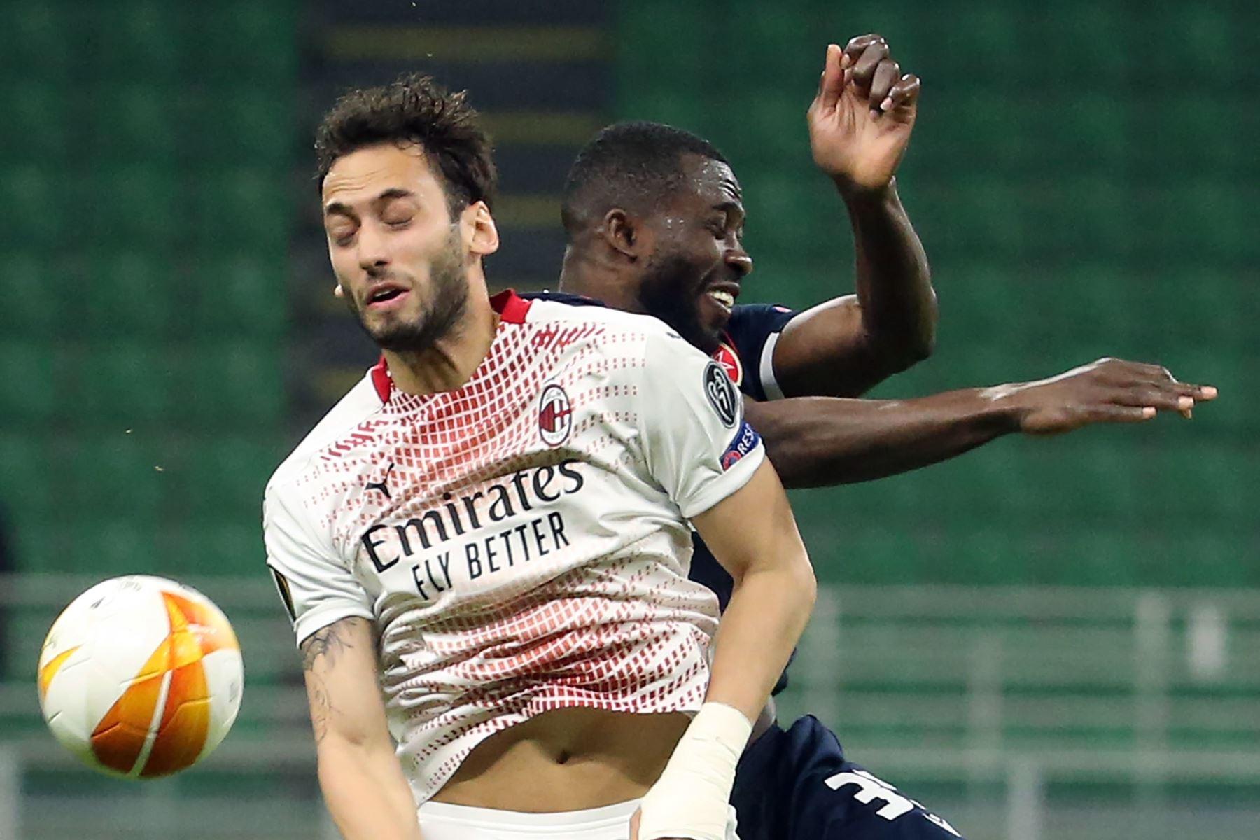Hakan Calhanoglu del AC Milan desafía el balón con Sekou Sanogo del Estrella Roja de Belgrado durante los dieciseisavos de final de la UEFA Europa League. Foto: EFE