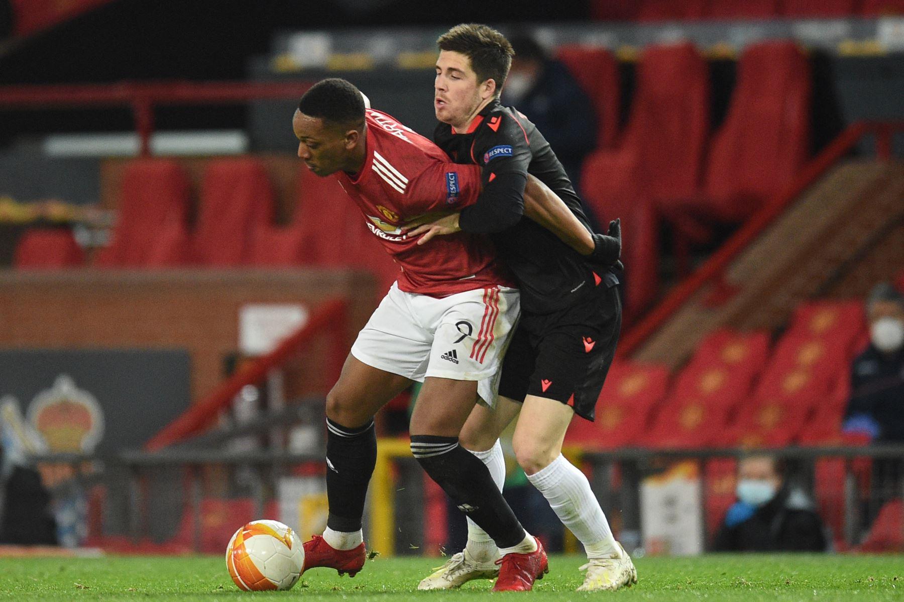 El delantero francés del Manchester United Anthony Martial detiene al centrocampista español de la Real Sociedad Igor Zubeldia durante la ronda de 32 de la UEFA Europa League. Foto: AFP