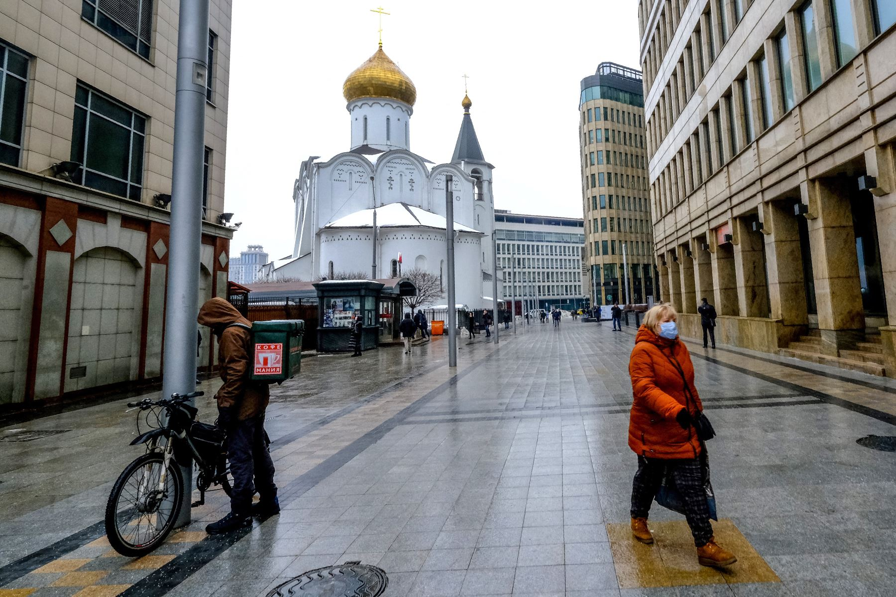 Una mujer con una mascarilla para protegerse contra la enfermedad del coronavirus camina por una calle en el centro de Moscú. Foto: AFP