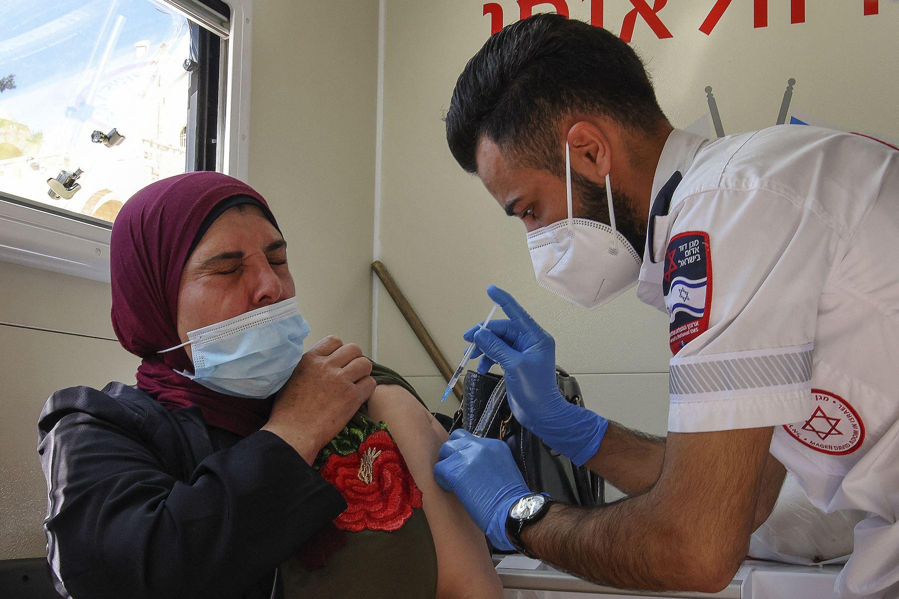 Un paramédico de los servicios médicos israelíes Magen David Adom vacuna a una mujer palestina en una clínica móvil el 26 de febrero de 2021 en la Puerta de Damasco en la Ciudad Vieja de Jerusalén. Foto: AFP