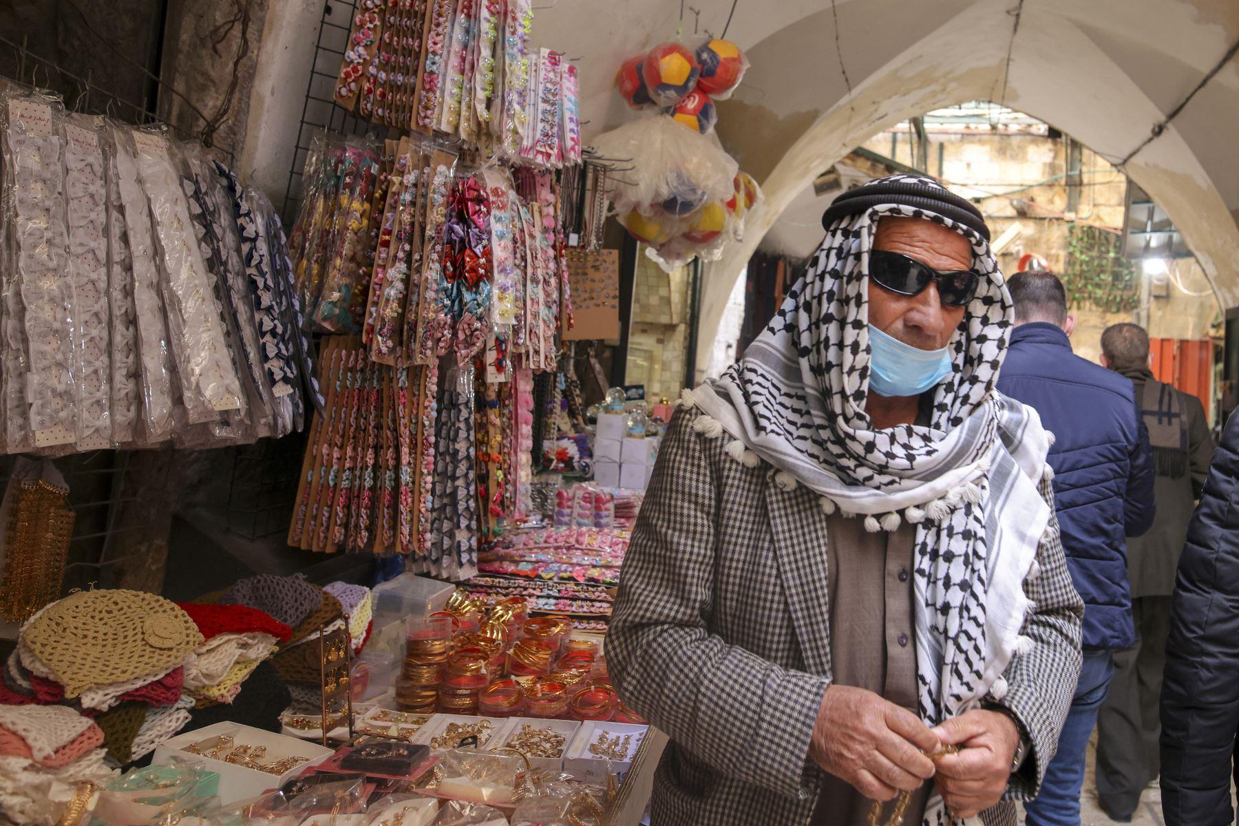 Un palestino vestido con una máscara pasa frente a las tiendas de la Ciudad Vieja de Jerusalén, en medio de la pandemia de coronavirus, el 24 de febrero de 2021. Foto: AFP