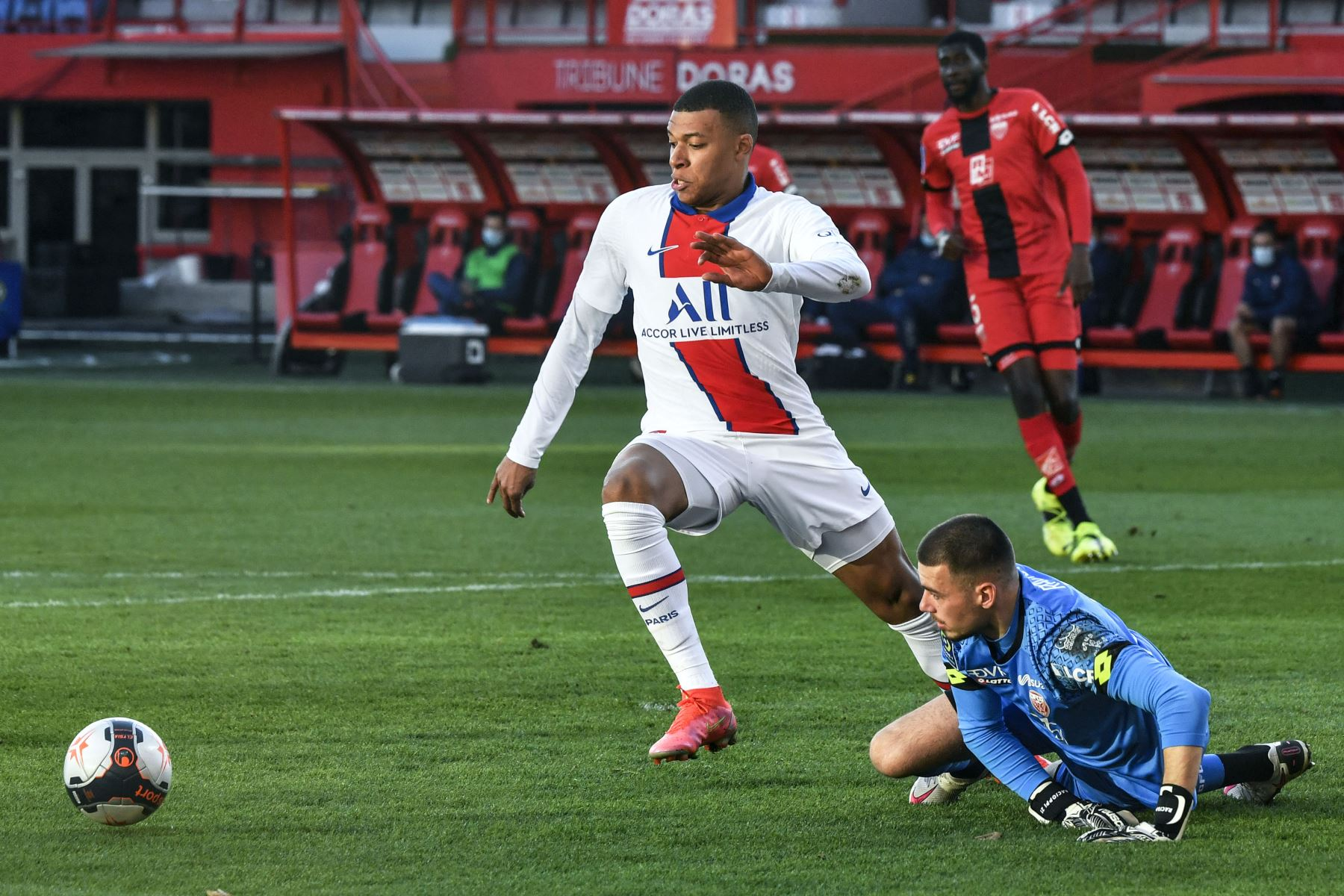 El delantero francés del Paris Saint-Germain Kylian Mbappé compite por el balón con el portero suizo de Dijon Anthony Racioppi durante el partido de fútbol francés L1 entre Dijon (DFCO) y Paris Saint-Germain (PSG). Foto: AFP