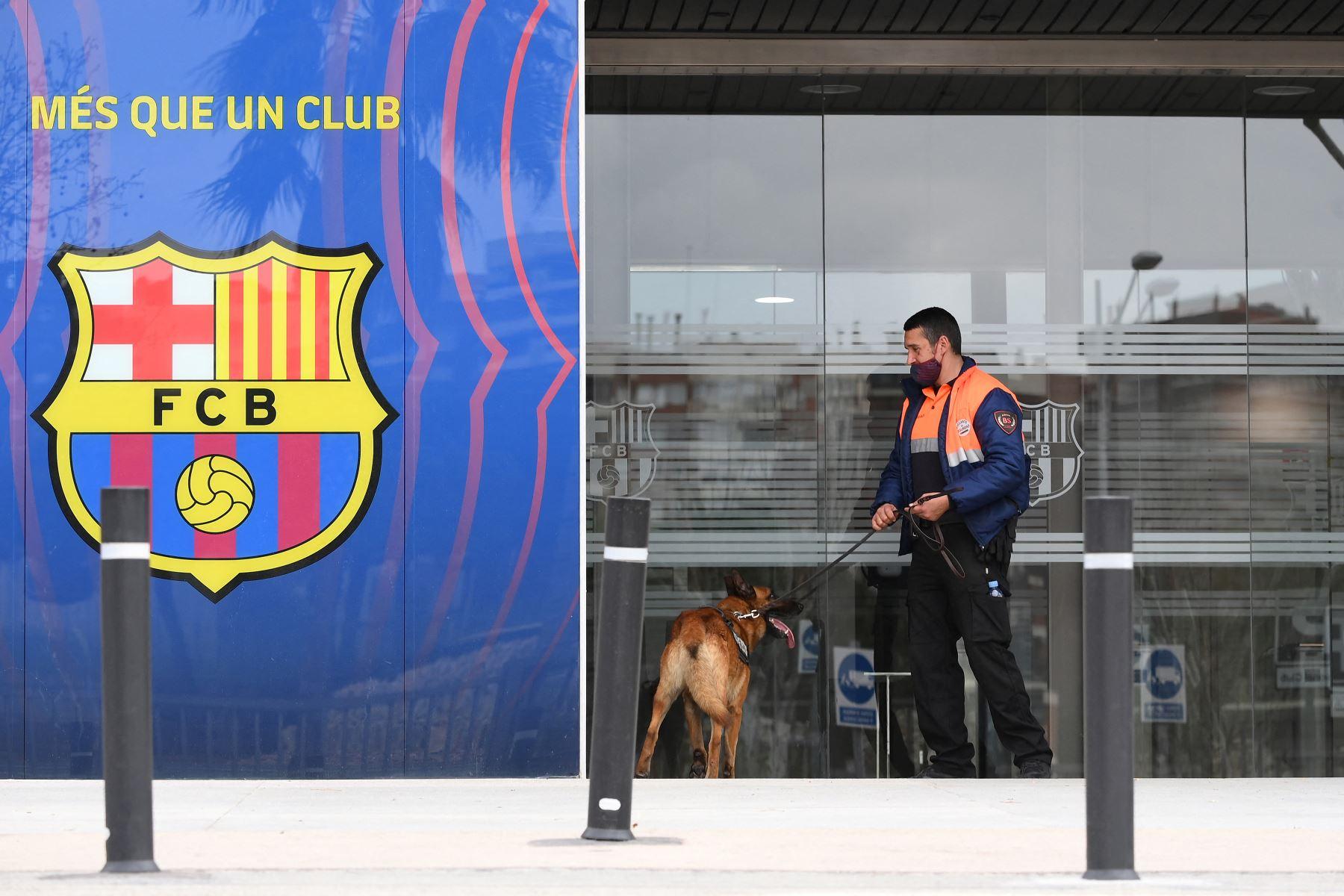 Un guardia de seguridad ingresa a las oficinas del Fútbol Club Barcelona con un perro el 1 de marzo de 2021 en Barcelona durante un operativo policial en el interior del edificio. Foto: AFP