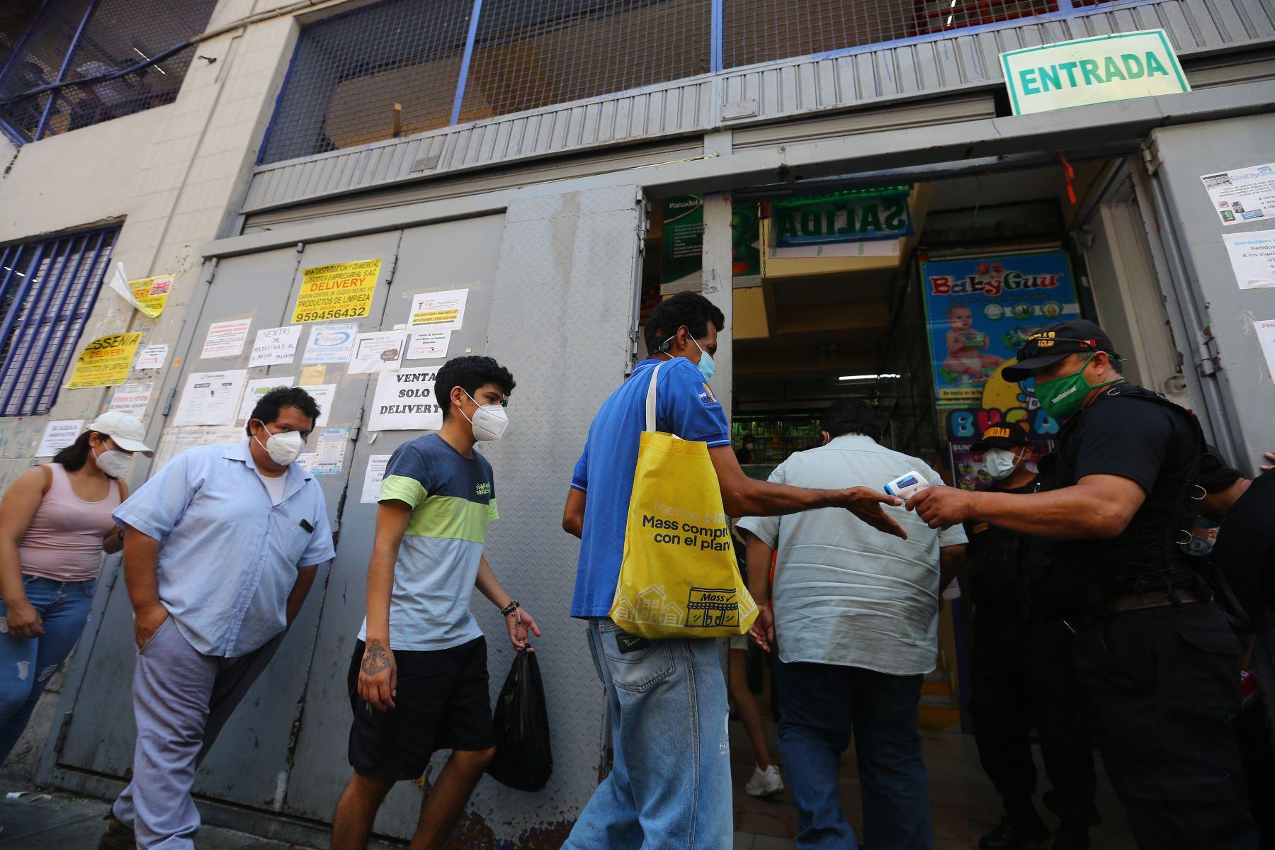 Encargados de la Seguridad controlan la temperatura de los clientes antes de ingresar a las galerias. Foto: ANDINA/Jhonel Rodríguez Robles