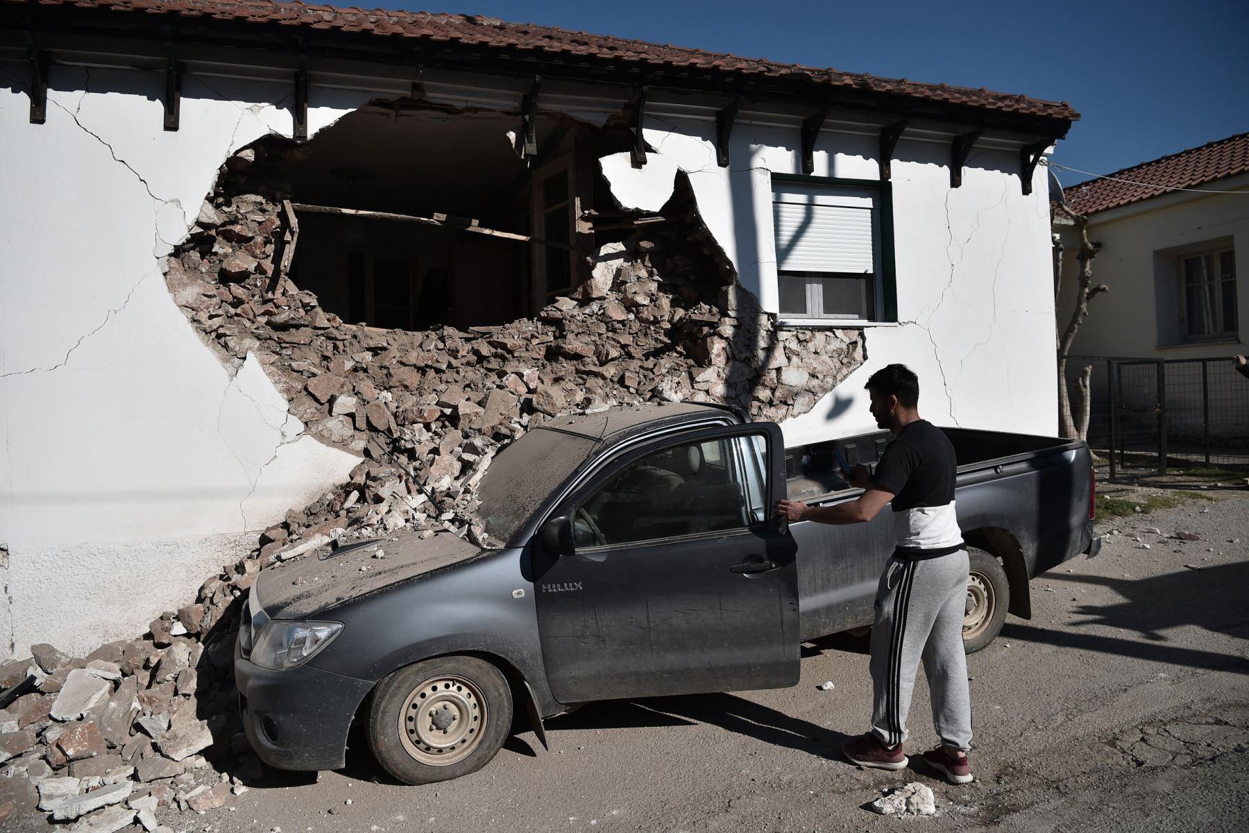Un hombre observa su automóvil después que un edificio se derrumbara parcialmente en el pueblo de Damasi debido al fuerte sismo de magnitud 6,3 en la región central griega de Tesalia. Foto: AFP