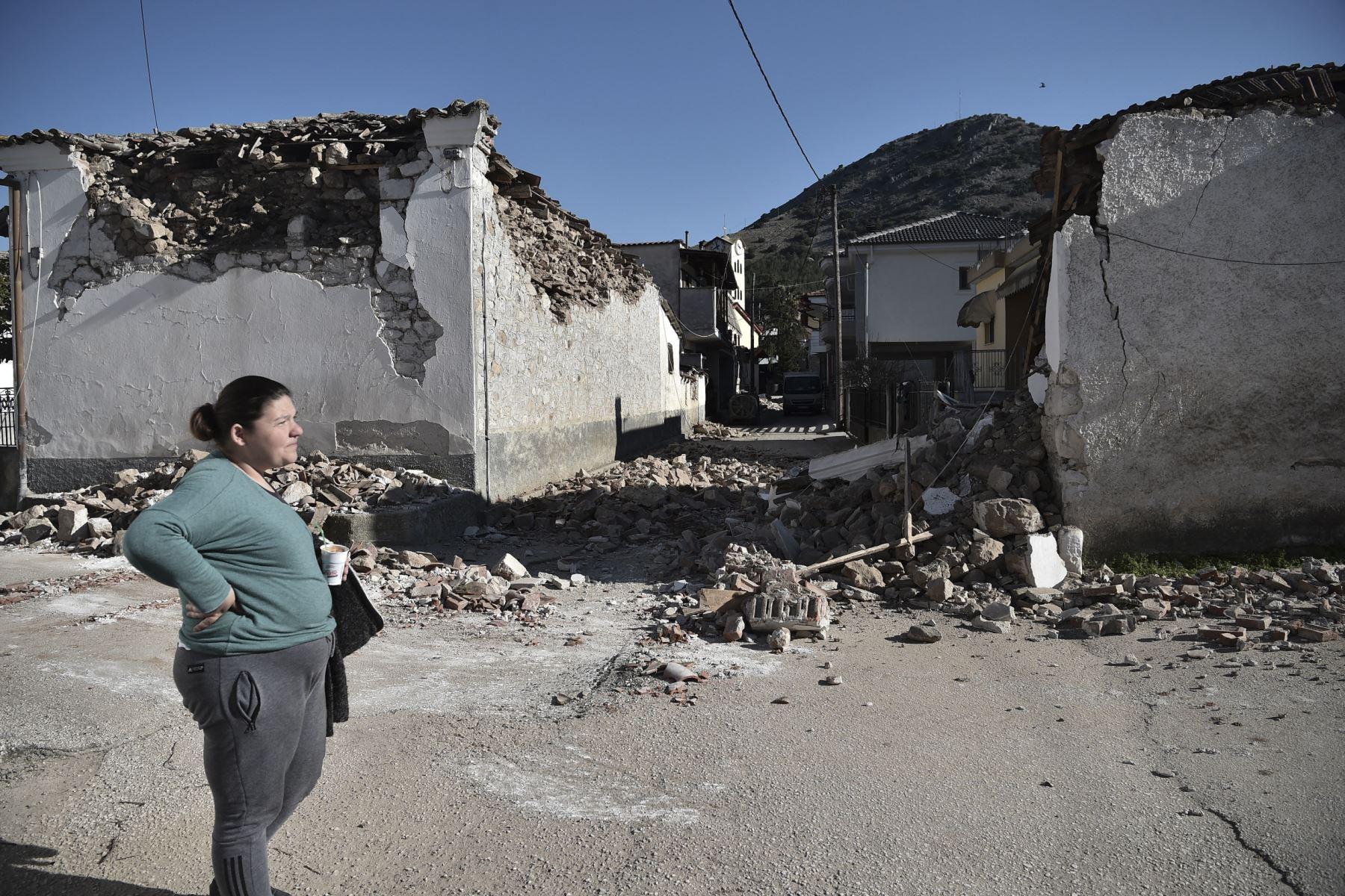 Una mujer se encuentra junto a los viejos edificios dañados en la aldea de Damasi después de que un fuerte sismo de magnitud 6,3 azotara la región central griega de Tesalia. Foto: AFP