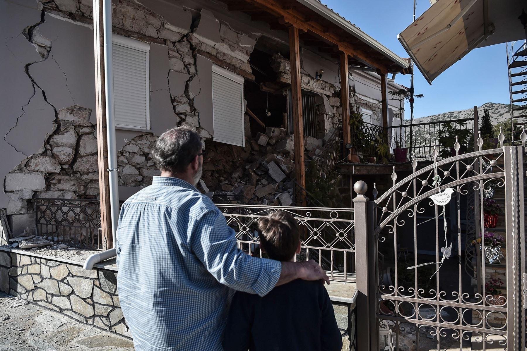 Un padre y un hijo observan una casa dañada en el pueblo de Damas después que un fuerte sismo de magnitud 6,3 azotara la región central griega de Tesalia. Foto: AFP
