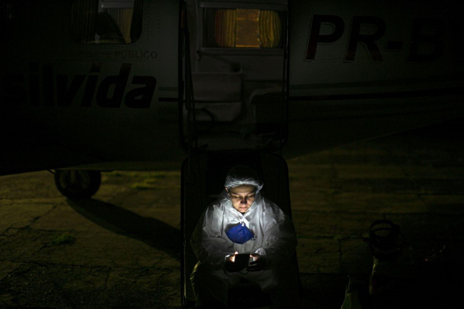 La enfermera Isabela revisa su teléfono móvil al pie de una ambulancia aérea de emergencia mientras espera que llegue un paciente con covid-19 de la Unidad de Atención de Emergencia en Santarem, estado de Pará, Brasil. Foto: AFP
