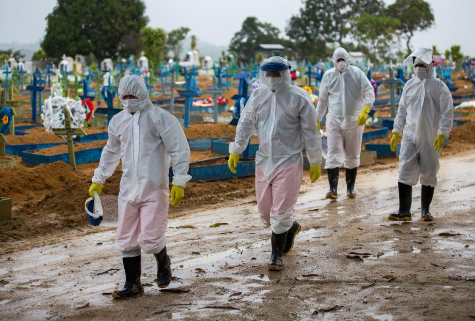 Trabajadores vestidos con trajes protectores caminan frente a las tumbas de las víctimas del covid-19 en el cementerio Nossa Senhora Aparecida, en Manaus, Brasil. Foto: AFP