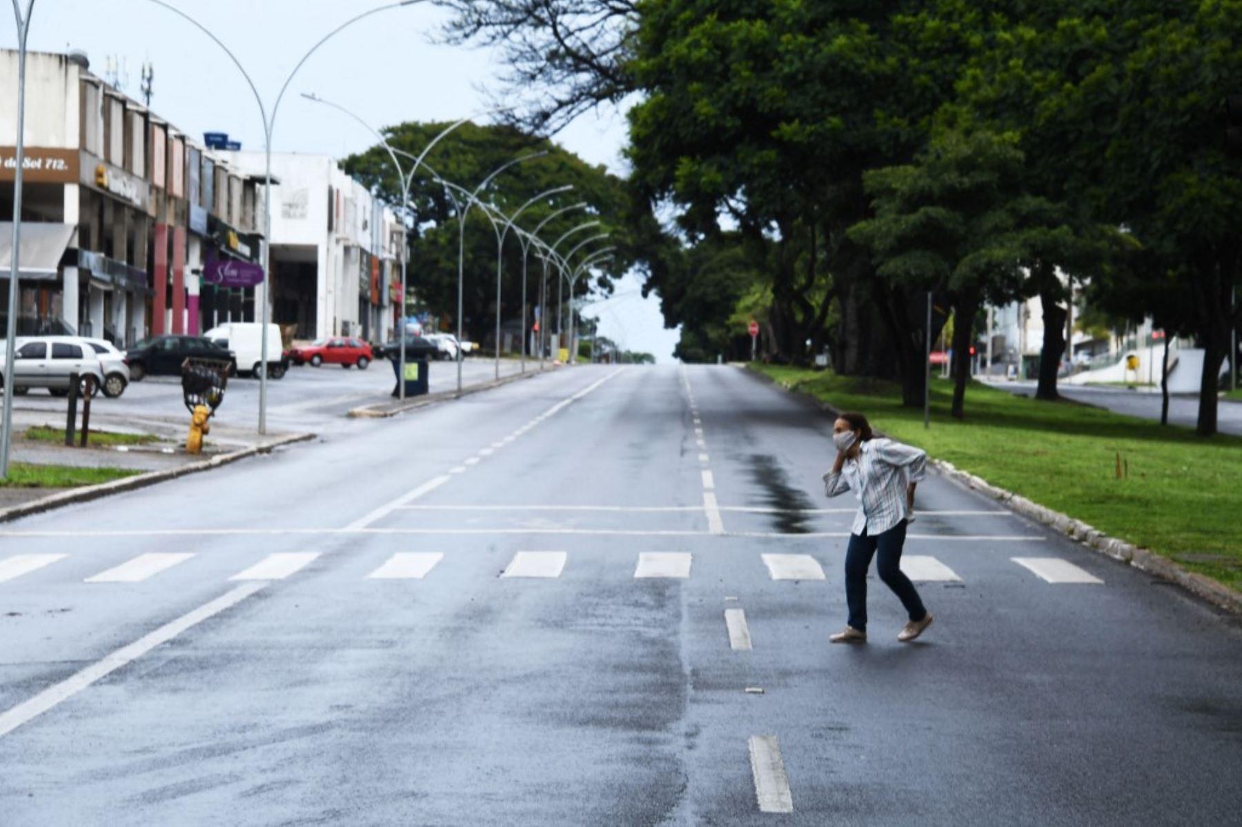 Una mujer cruza una calle en una zona comercial de Brasilia, en el primer día de encierro en la capital brasileña decretado por el gobernador Ibanes Rocha para combatir un aumento de casos del nuevo coronavirus, covid-19. Foto: AFP