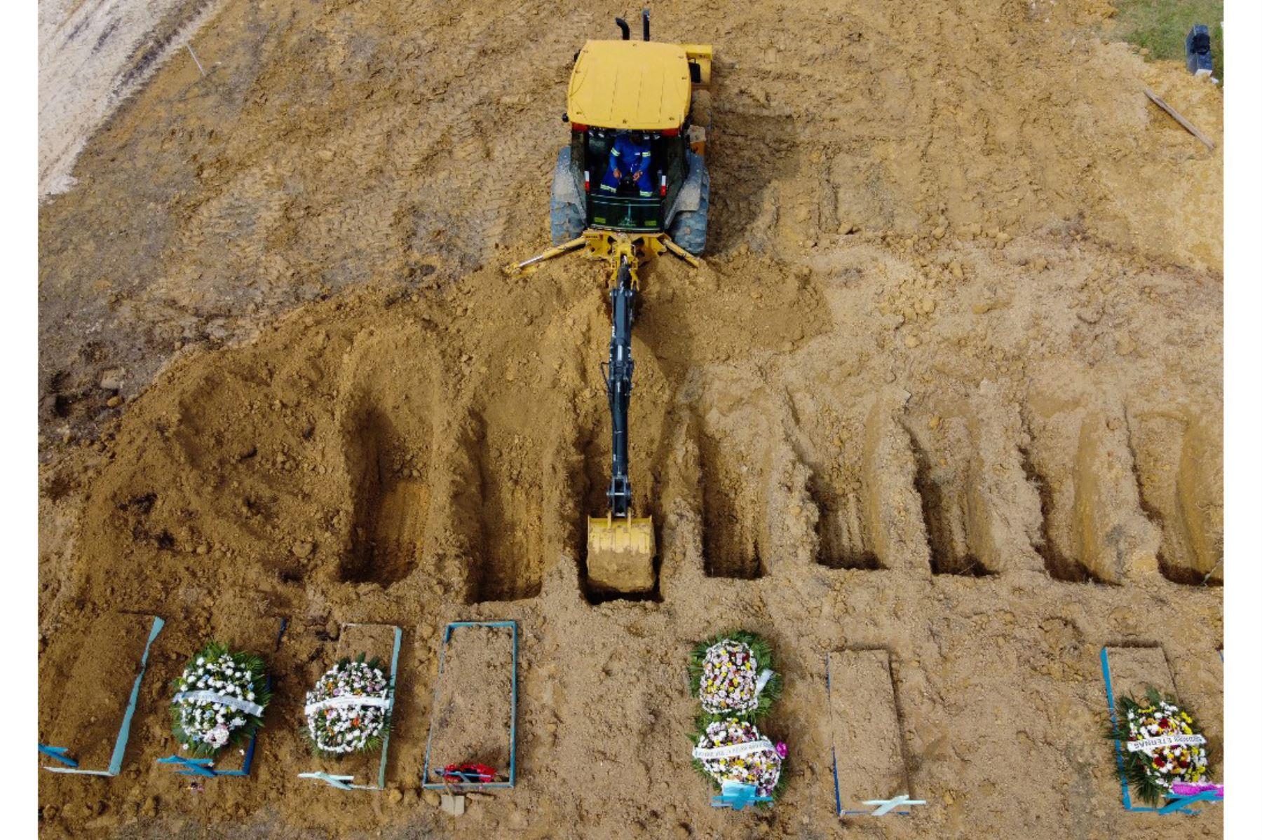 Esta foto de archivo tomada el 8 de enero de 2021 muestra una vista aérea de un tractor cavando tumbas en una nueva área del cementerio Nossa Senhora Aparecida reservada para las víctimas del covid-19, en Manaus, Brasil. Foto: AFP
