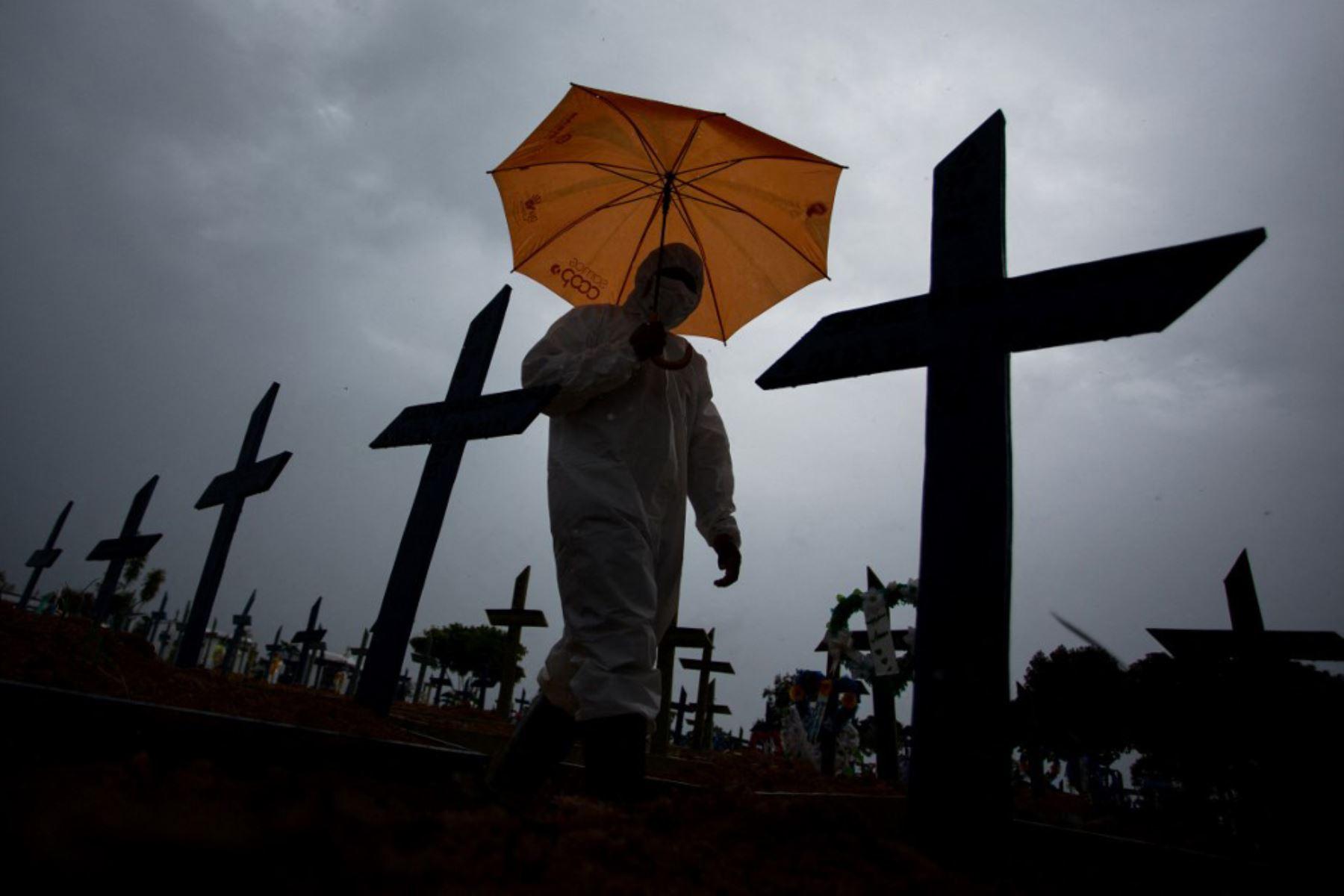Un trabajador vestido con un traje protector y portando un paraguas pasa junto a las tumbas de las víctimas del covid-19 en el cementerio Nossa Senhora Aparecida, en Manaus, Brasil. Foto: AFP