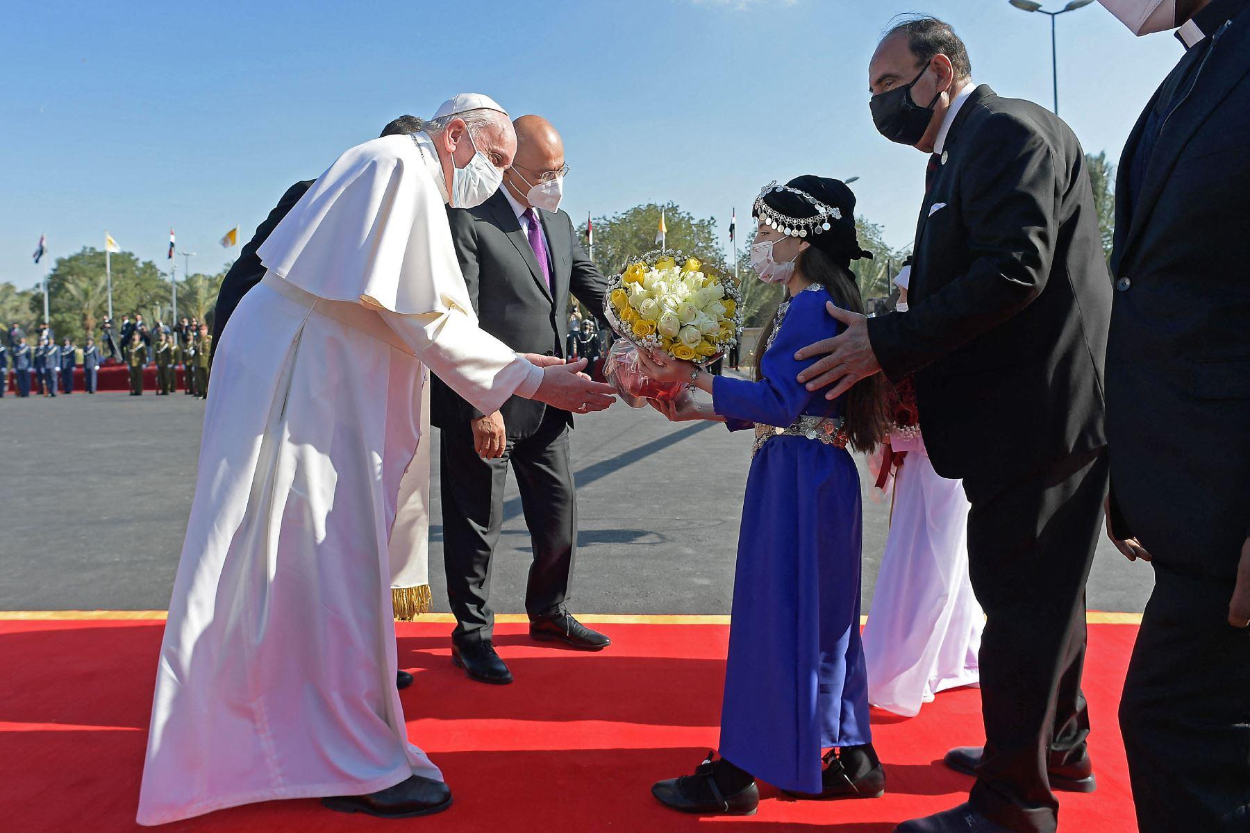 Una niña iraquí con un traje tradicional ofrece al Papa Francisco un ramo de flores en el aeropuerto de Bagdad a su llegada el 5 de marzo de 2021 en la primera visita papal. Foto: AFP