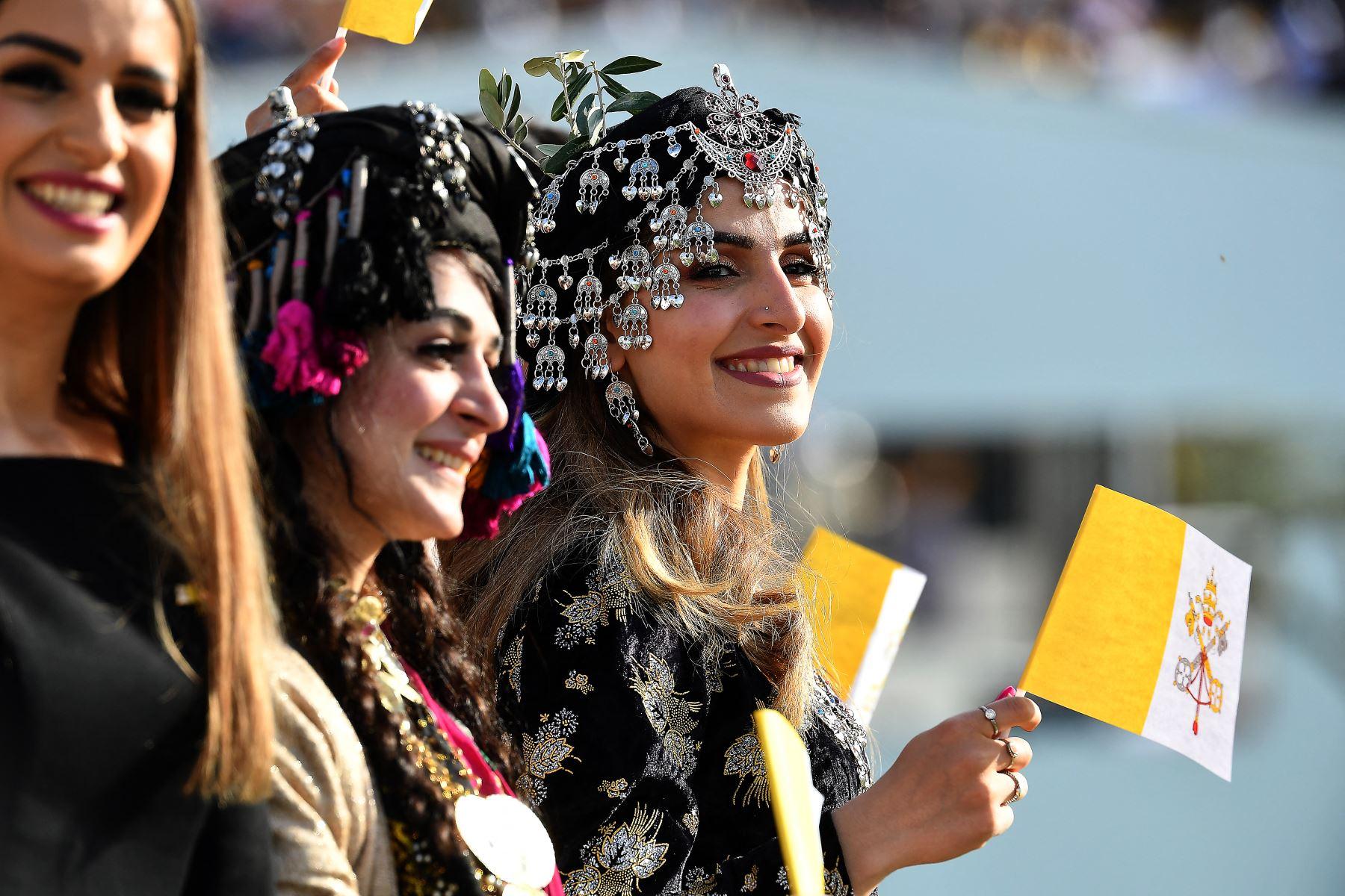 Mujeres jóvenes vestidas con ropa tradicional kurda ondean banderas de la Santa Sede mientras esperan la llegada del Papa Francisco al Estadio Franso Hariri en Arbil, en la capital de la región autónoma kurda del norte de Irak.  Foto: AFP