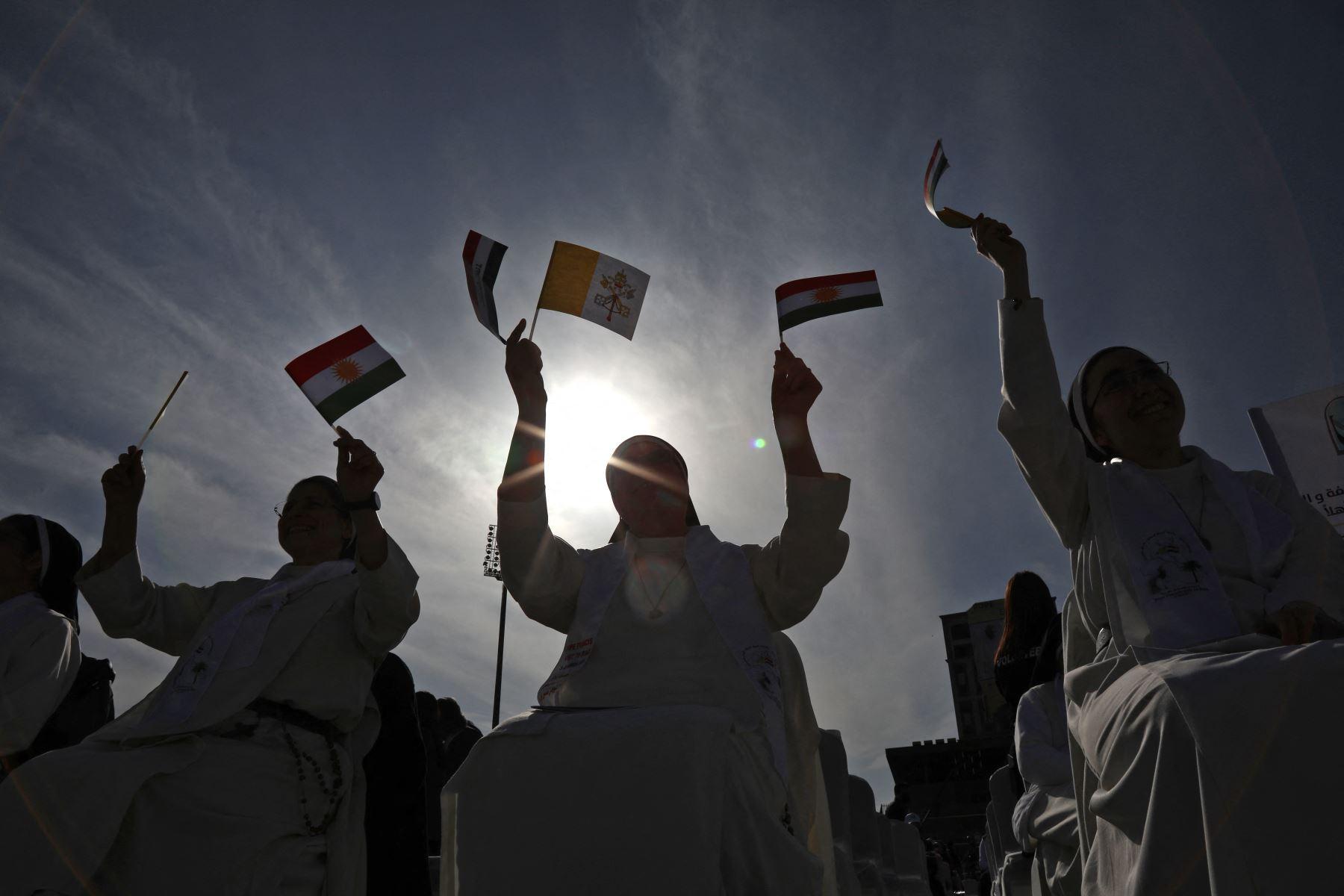 Una monja ondea banderas de Irak, Kurdistán y la Santa Sede mientras espera la llegada del Papa Francisco al Estadio Franso Hariri en Arbil, en la capital de la región autónoma kurda del norte de Irak.  Foto: AFP