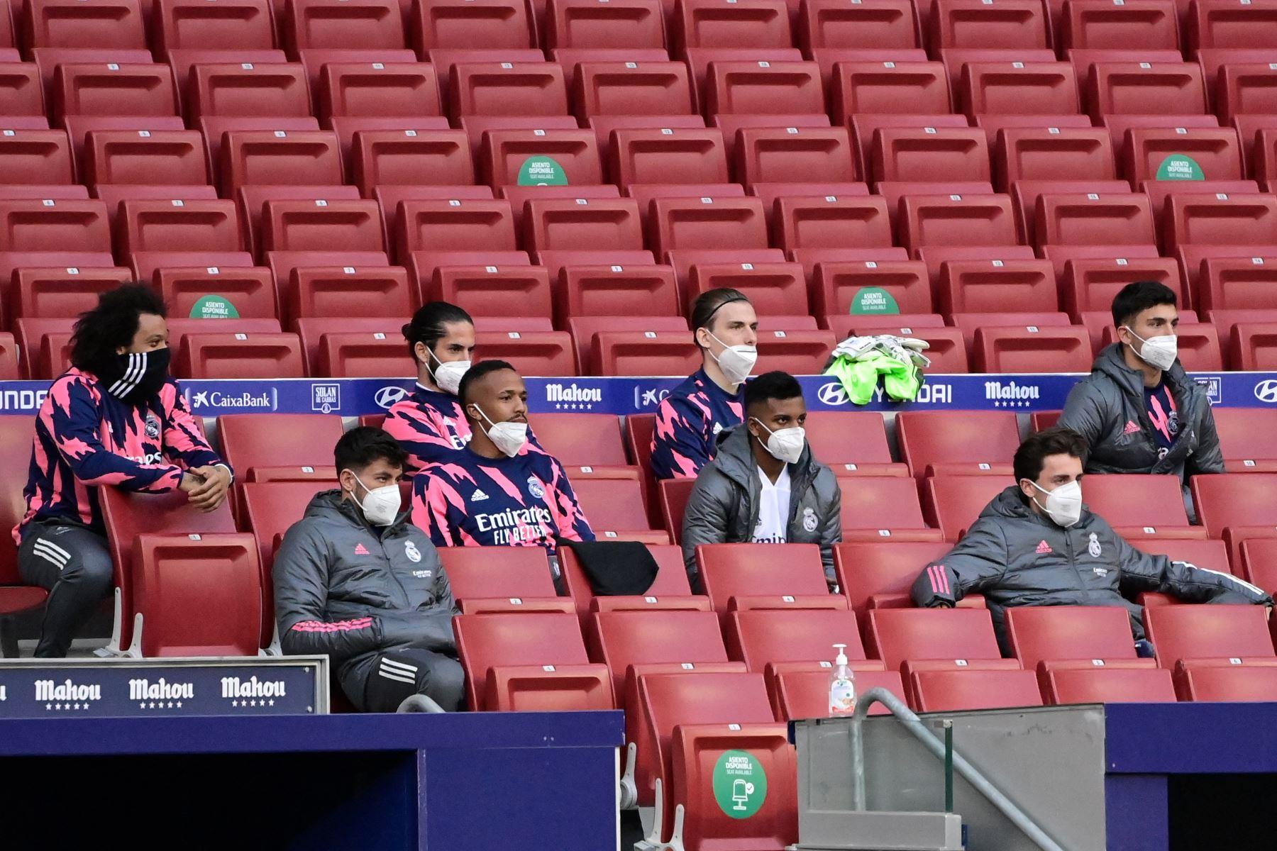 Los jugadores del Real Madrid se sientan con máscaras durante el partido de fútbol de la liga española Club Atlético de Madrid contra el Real Madrid CF en el estadio Wanda Metropolitano de Madrid. Foto: AFP
