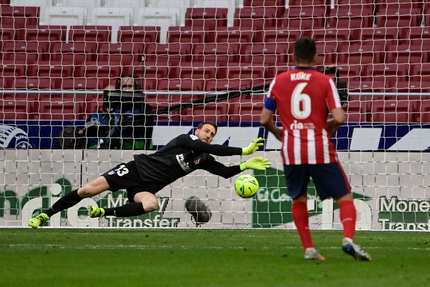 El portero esloveno del Atlético de Madrid, Jan Oblak, se lanza por el balón durante el partido de fútbol de la liga española Club Atlético de Madrid contra el Real Madrid. Foto: AFP