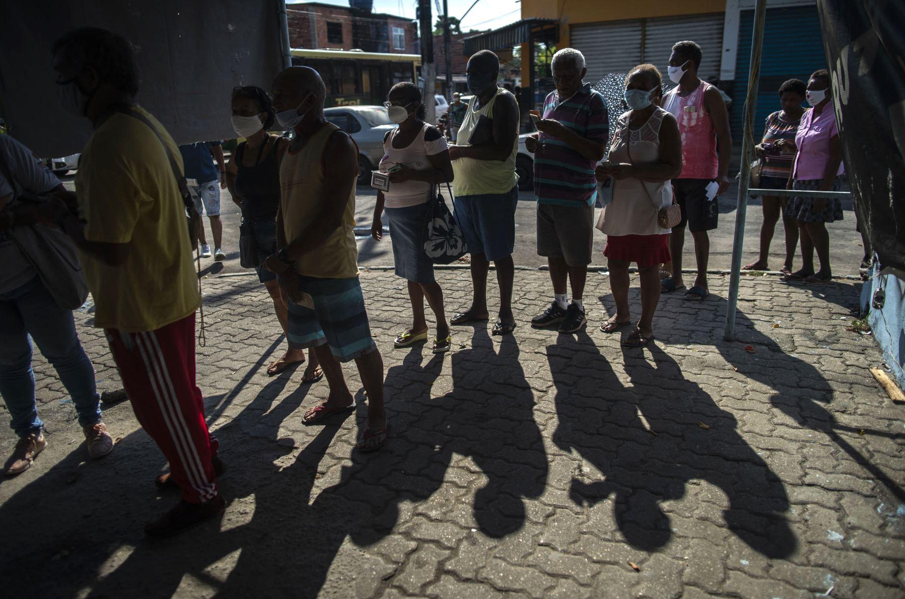 Personas con mascarillas hacen cola para recibir una dosis de la vacuna de covid-19 en un centro de vacunación en la plaza Cangulo, barrio Saracuruna, en Duque de Caxias, estado de Río de Janeiro, Brasil. Foto: AFP