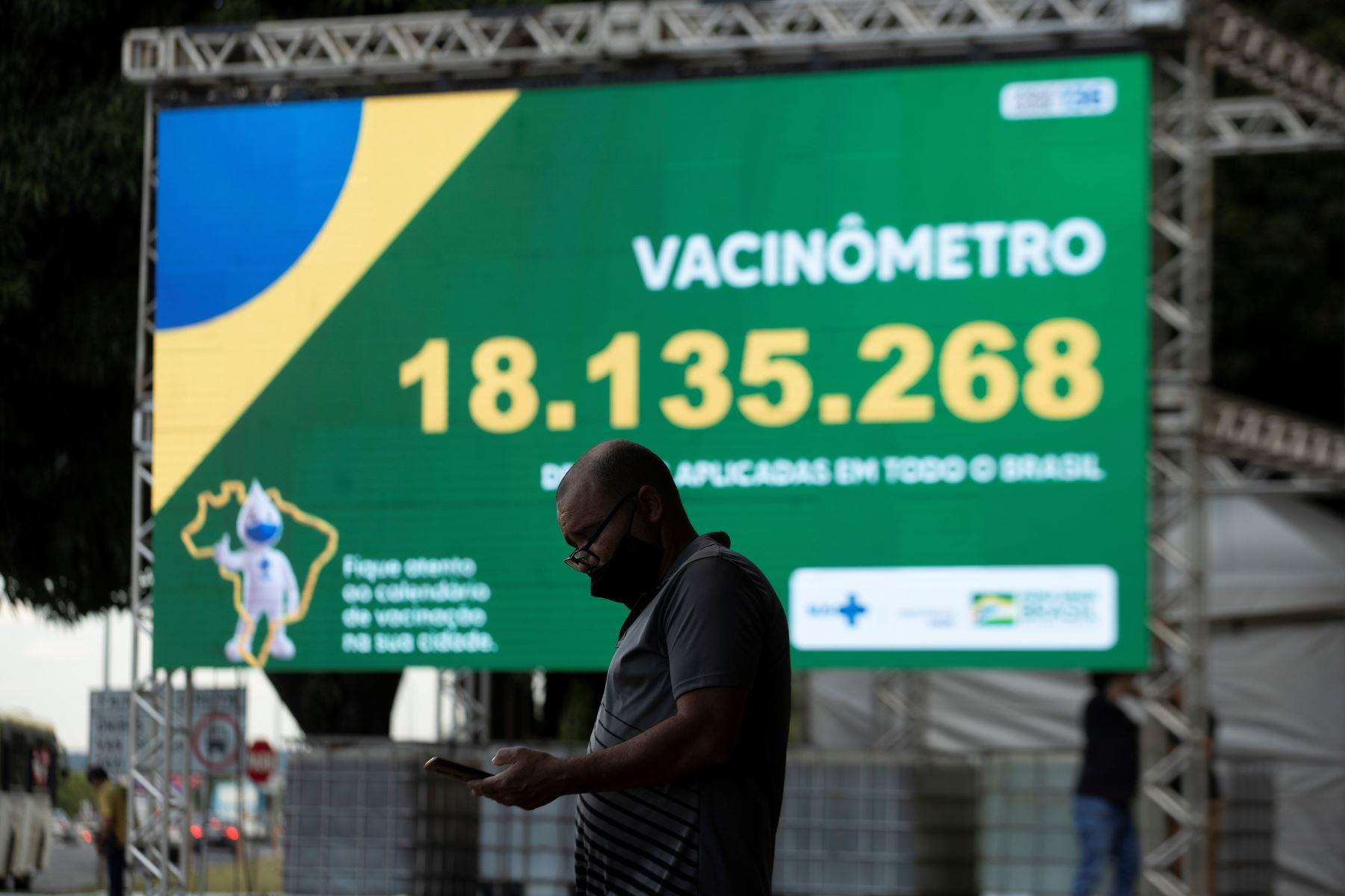 """Un hombre observa su teléfono frente al """"vacunómetro"""", un tablero digital donde se registra el número de personas vacunadas en Brasilia, el 30 de marzo del 2021. Foto: EFE"""