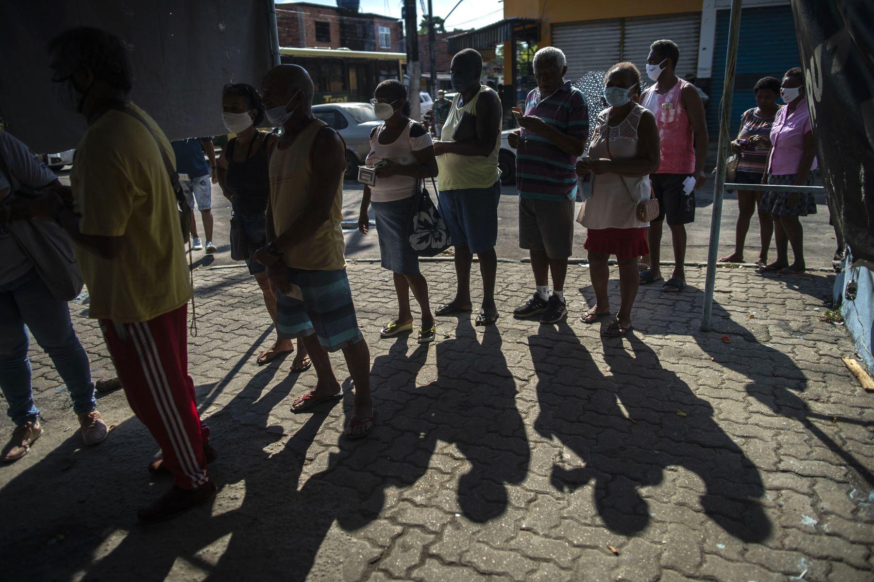 Personas con mascarillas hacen cola para su turno para recibir una dosis de la vacuna COVID-19 en un centro de vacunación en la plaza Cangulo, barrio Saracuruna, en Duque de Caxias, estado de Río de Janeiro, Brasil, el 30 de marzo de 2021. Foto: AFP