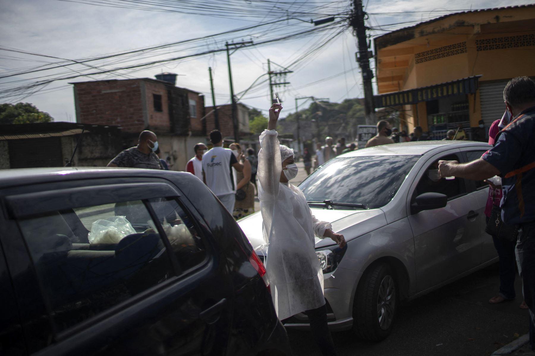 Un trabajador de salud sostiene una jeringa con una dosis de la vacuna COVID-19 en un centro de vacunación en la plaza Cangulo, en Duque de Caxias, estado de Río de Janeiro, Brasil, el 30 de marzo de 2021. Foto: AFP