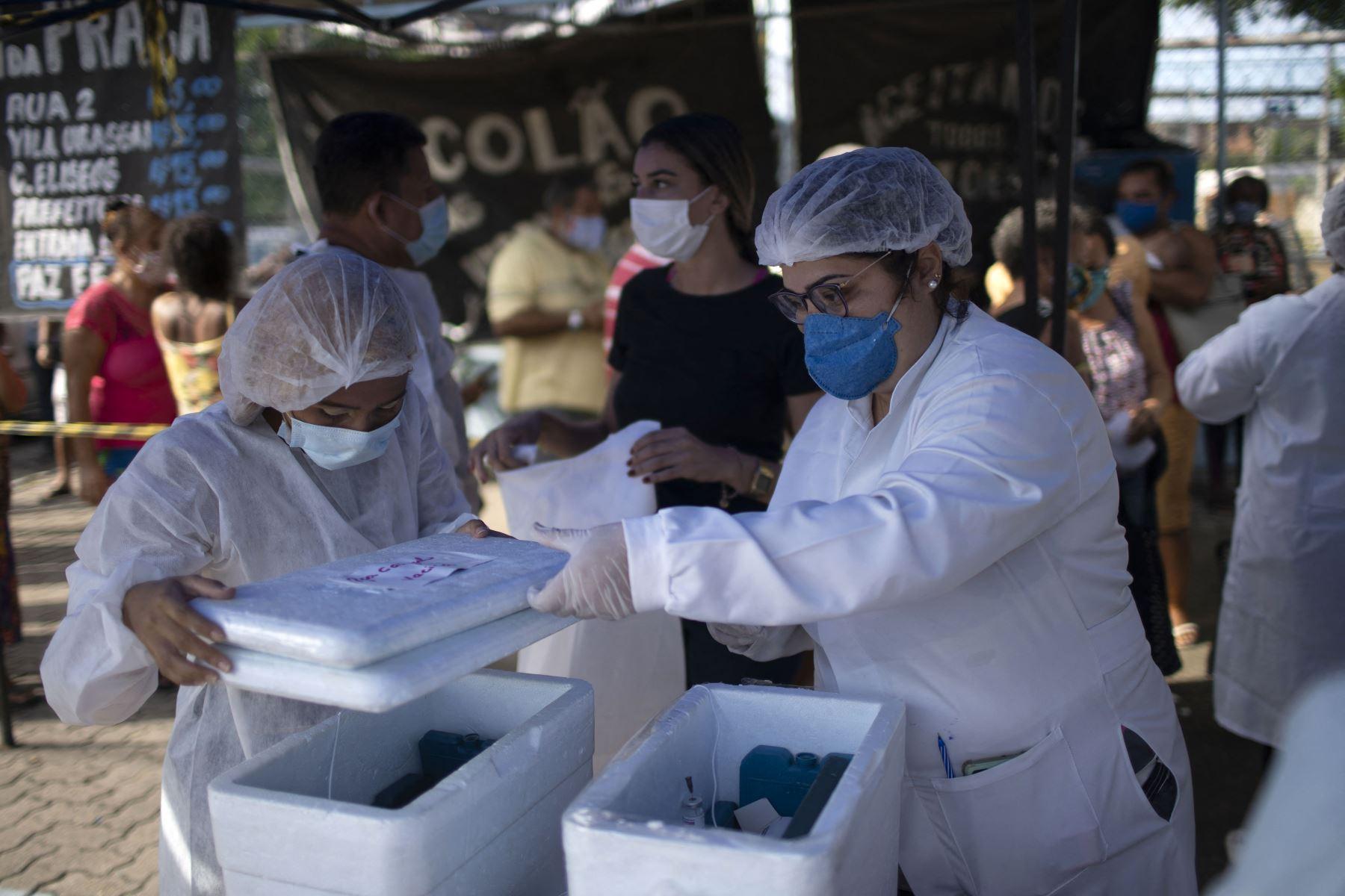 Trabajadores de salud preparan dosis de la vacuna COVID-19 en un centro de vacunación de la plaza Cangulo, en Duque de Caxias, estado de Río de Janeiro, Brasil, el 30 de marzo de 2021. Foto: AFP