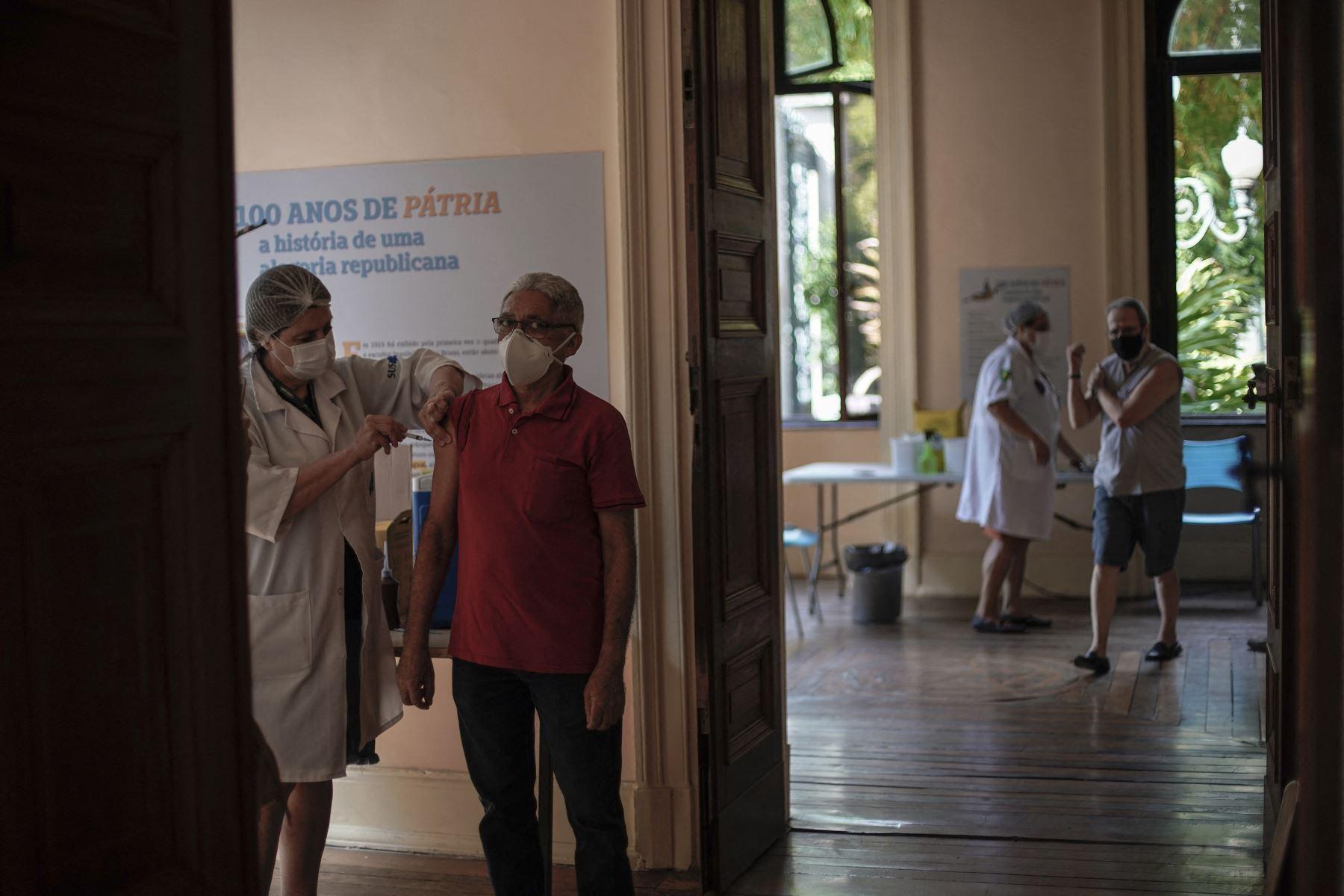 Dos hombres son inoculados contra el nuevo coronavirus con la vacuna Sinovac CoronaVac de China producida por Butantan, el mayor productor de vacunas de Brasil, en un centro de vacunación instalado en el Palacio de Catete, en Río de Janeiro, el 31 de marzo de 2021. Foto: AFP