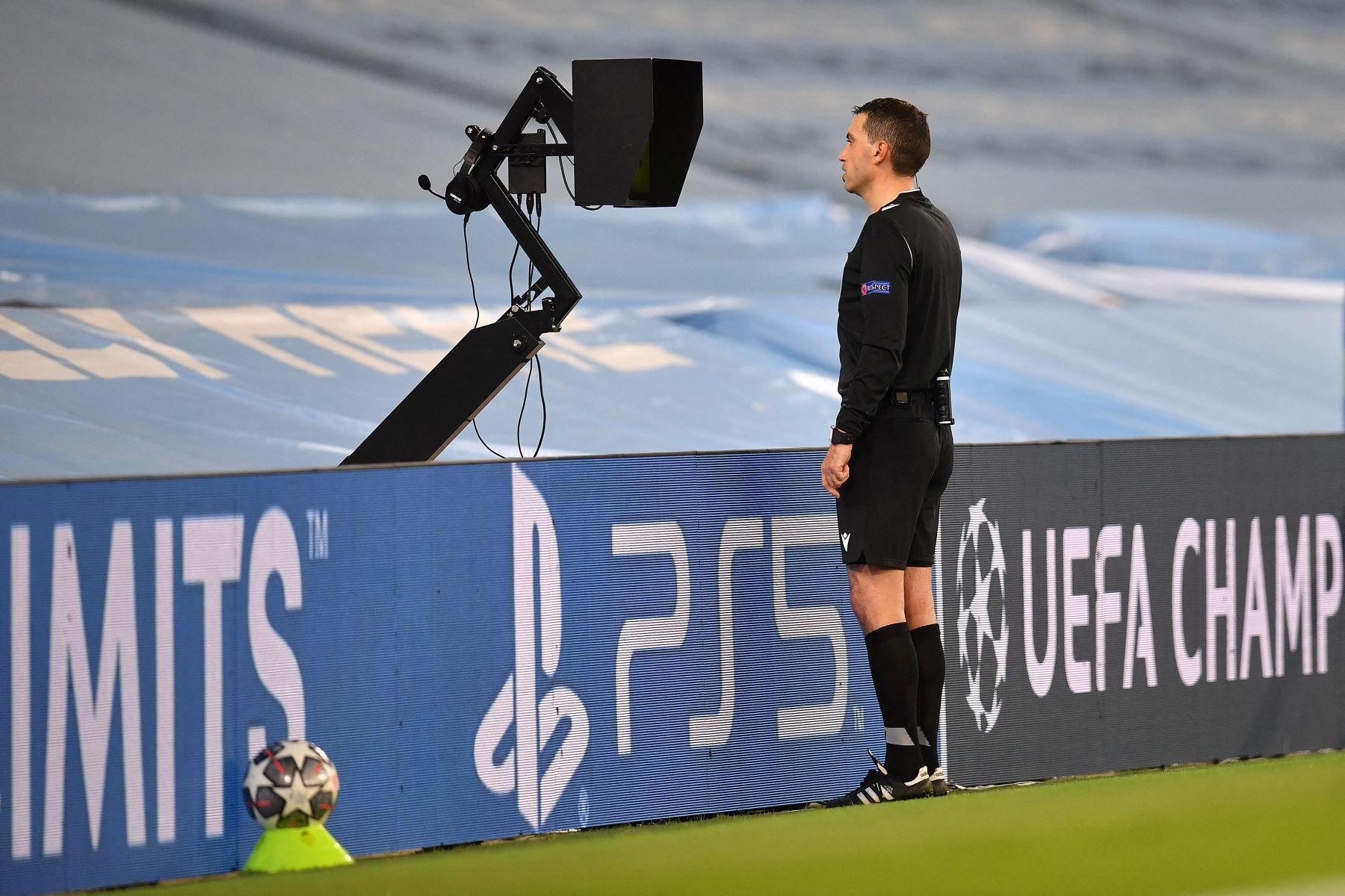El árbitro Ovidiu Hategan revisa la pantalla del VAR antes de anular su decisión de penalti durante el partido de ida de cuartos de final de la UEFA Champions League. Foto: AFP