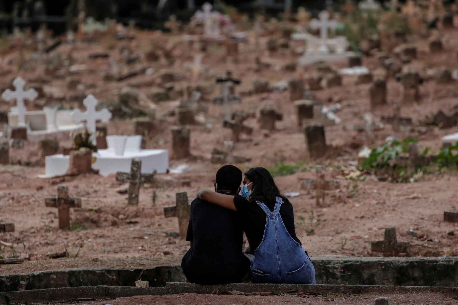 Una pareja llora a una mujer víctima de la COVID-19 que fue sepultada el 6 de abril del 2021 en un cementerio de Río de Janeiro, en Brasil.
