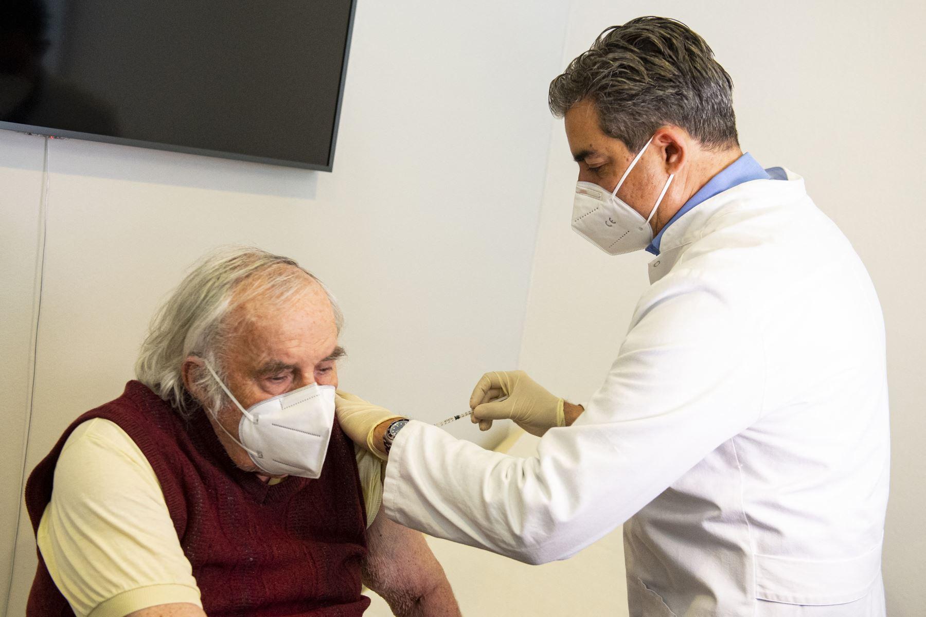 El médico general Oliver Abbushi vacuna al paciente Helmuth Mueller con la vacuna de AstraZeneca contra el coronavirus en Deisenhofen, sur de Alemania, el 31 de marzo de 2021. Foto: AFP