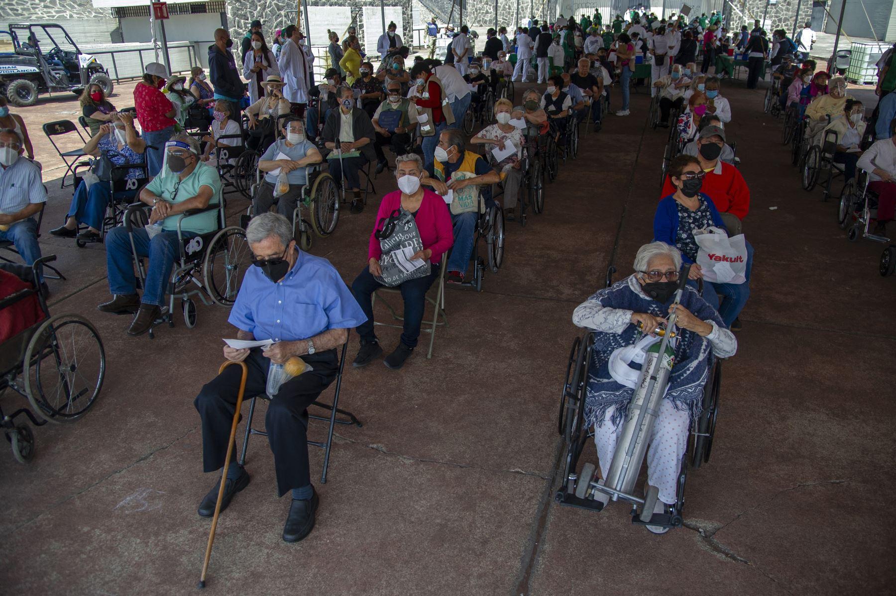 Ancianos descansan luego de recibir dosis de la vacuna AstraZeneca contra COVID-19 en un centro de vacunación instalado en el Estadio Olímpico Universitario de la colonia Coyoacán, en la Ciudad de México, el 30 de marzo de 2021. Foto: AFP