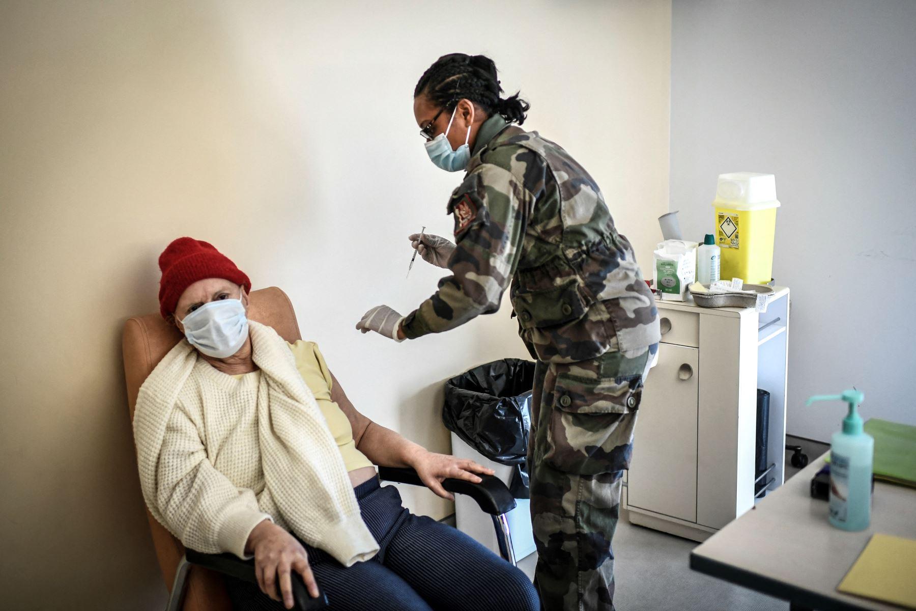 Una mujer se prepara para recibir una dosis de la vacuna Pfizer-BioNTech contra el Covid-19 en el hospital militar Begin en Saint-Mande, al este de París, el 07 de abril del 2021. Foto: AFP