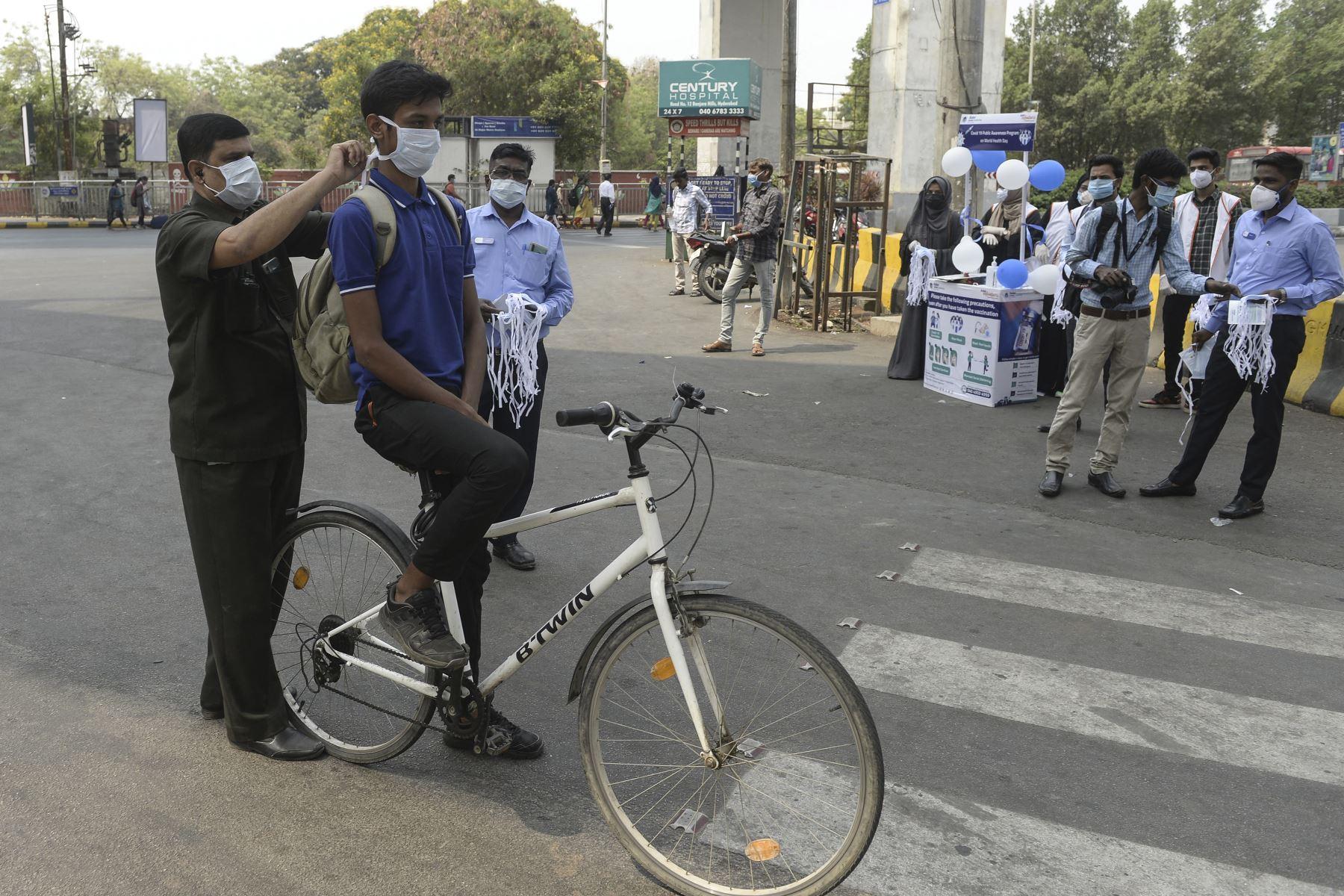 Un trabajador de la salud ayuda a un ciclista a ponerse una mascarilla durante una campaña de concientización contra la propagación del coronavirus Covid-19, en Hyderabad, India. Foto: AFP