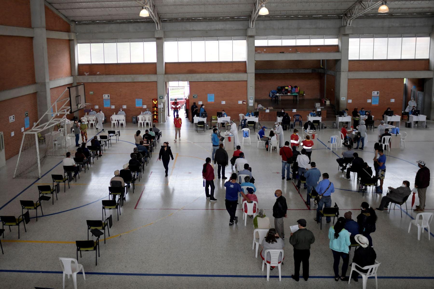 La gente espera ser inoculada con la vacuna Oxford AstraZeneca contra COVID-19 en medio de la pandemia del nuevo coronavirus, en Bogotá el 5 de abril de 2021. Foto: AFP