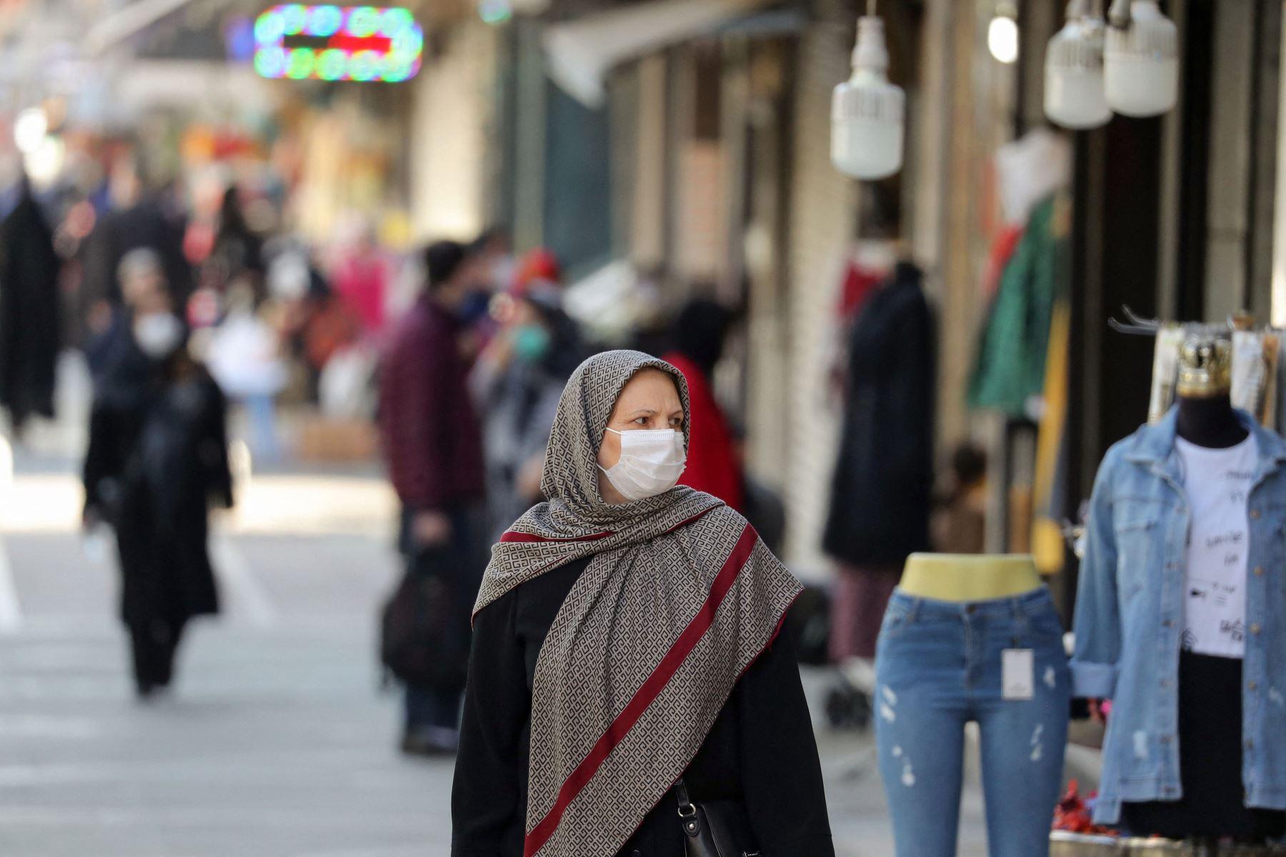 Los iraníes caminan con máscaras faciales por las calles de la capital, Teherán, en medio de la pandemia del coronavirus. Foto: AFP