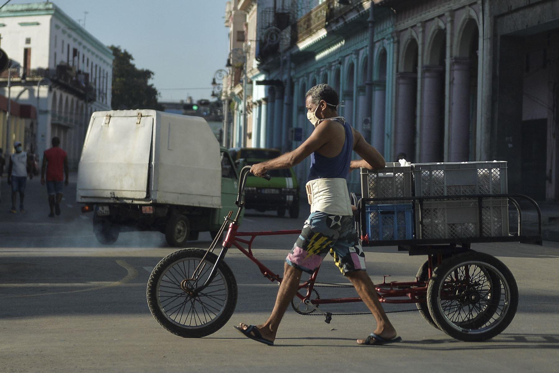Un hombre con mascarilla transporta alimentos en su bicicleta por una calle de La Habana, el 6 de abril de 2021: Foto. AFP