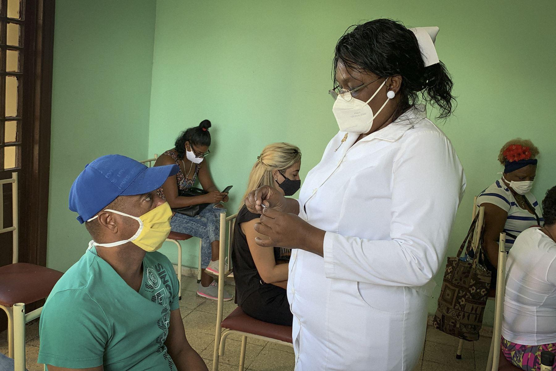 Una enfermera controla la temperatura de los cubanos pertenecientes al sistema de salud quienes esperan ser inoculados con la vacuna cubana Soberana 2, el 24 de marzo de 2021, en la Havana. Foto: AFP