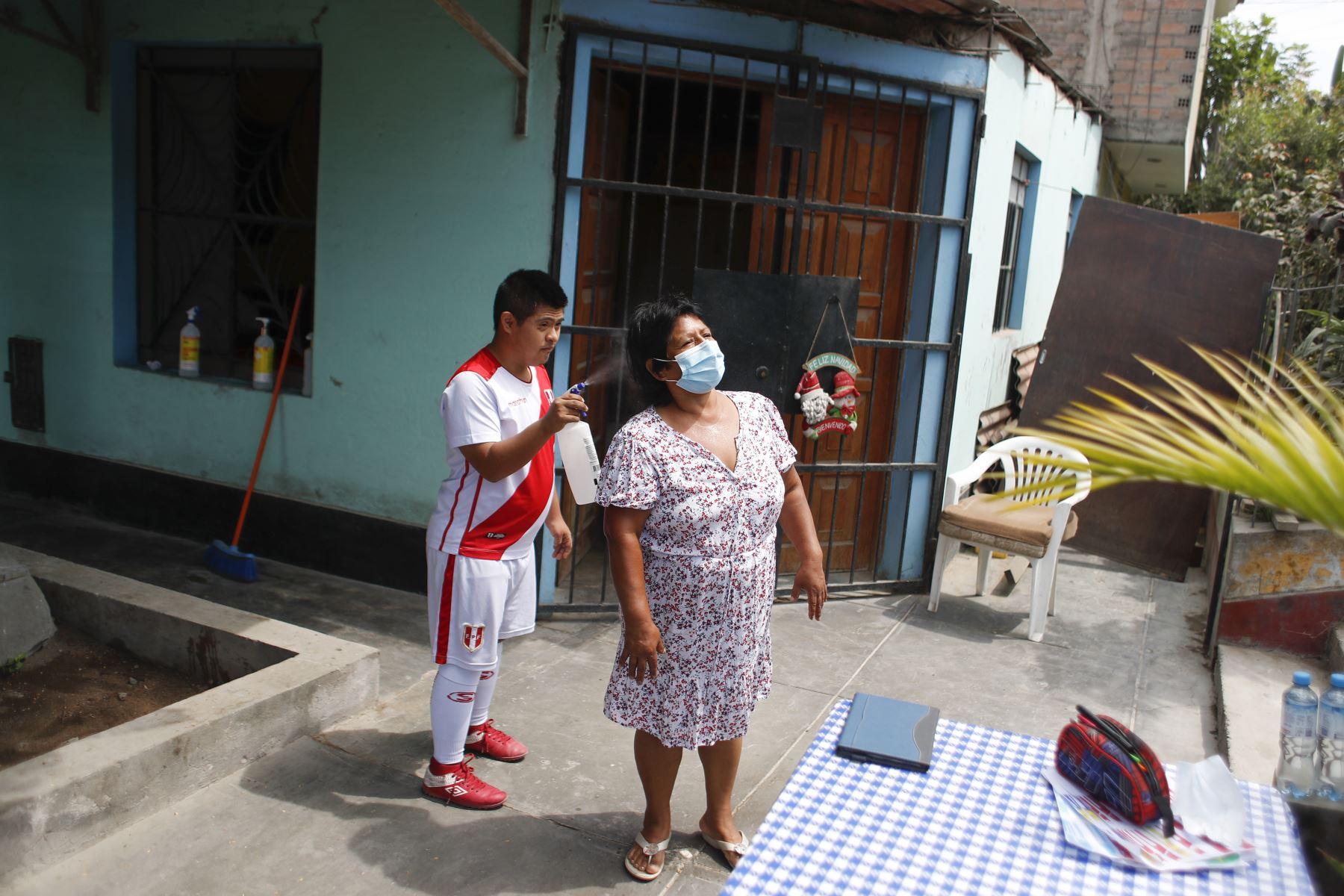 Joseph Flores se encarga de rociar alcohol cada vez que algún familiar regresa a casa. Foto: ANDINA/Renato Pajuelo