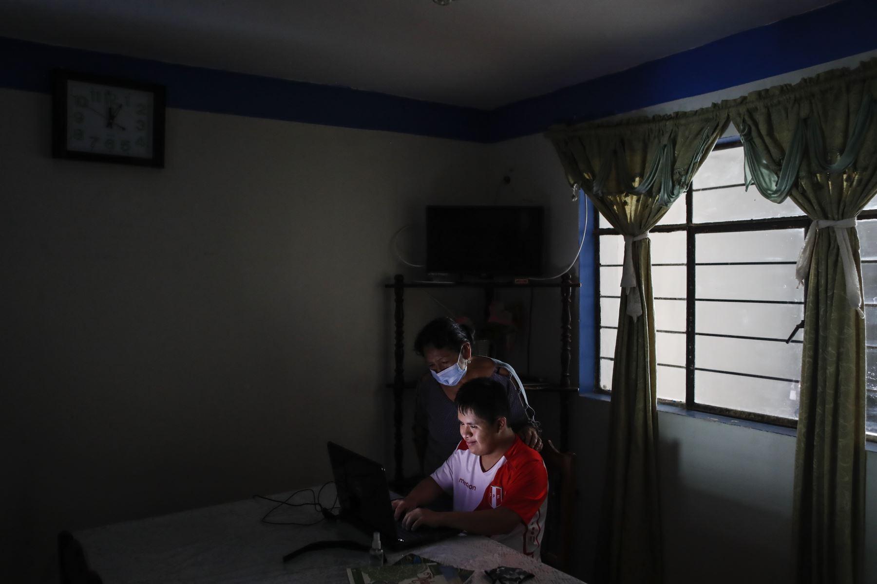 Ronny Flores enseña a su madre algunos videos de sus jugadores favoritos en Youtube. Foto: ANDINA/Renato Pajuelo