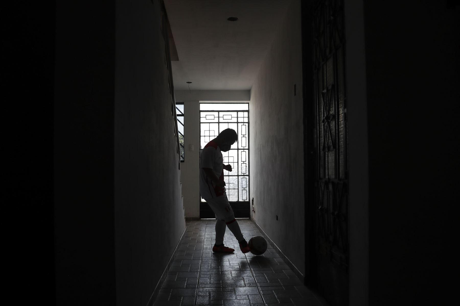 Ronny Flores practica algunas tiros contra la pared en el pasillo de su hogar debido al confinamiento que acata, en Villa El Salvador. Foto: ANDINA/Renato Pajuelo