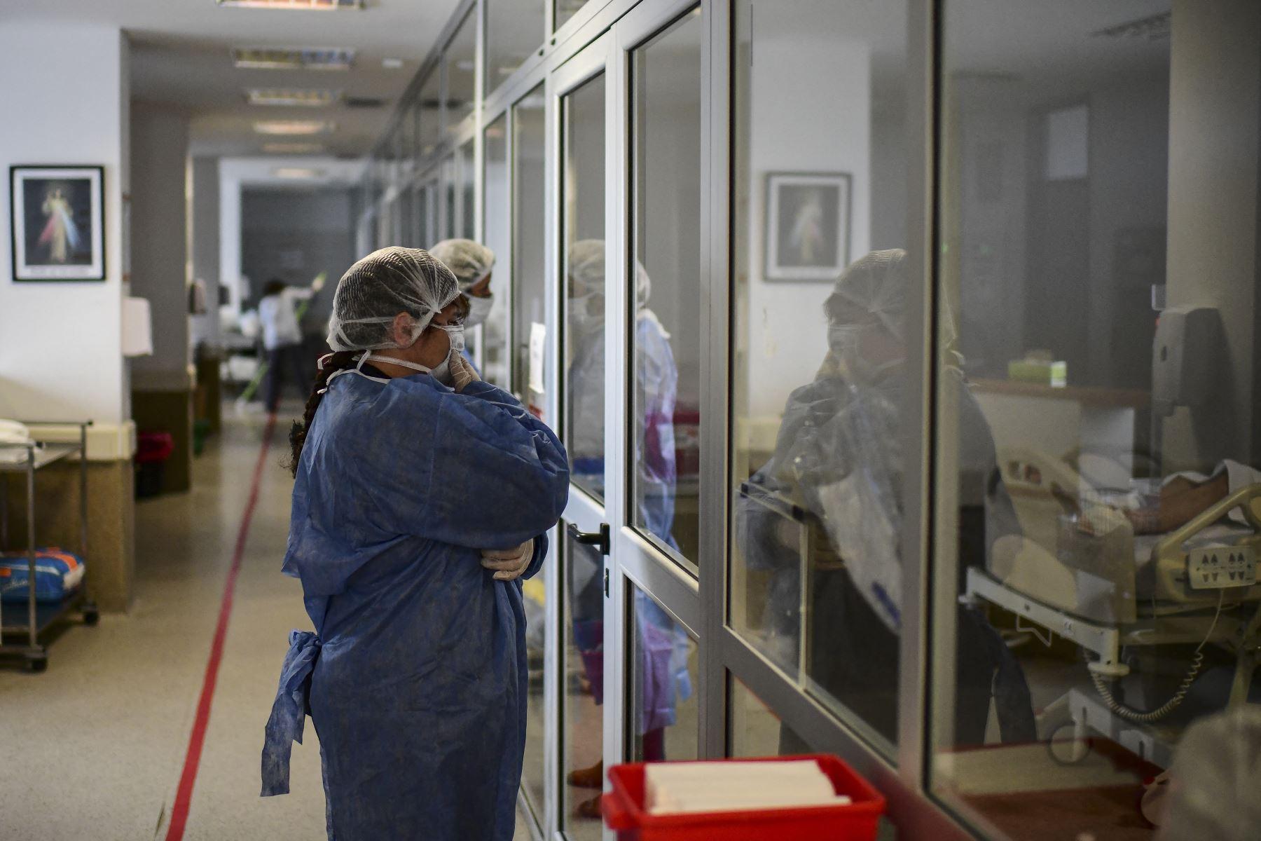 Una mujer reza mientras visita a un familiar infectado con COVID-19 en la Unidad de Cuidados Intensivos del Hospital El Cruce - Dr. Nestor Kirchner en Florencio Varela, Argentina el 13 de abril de 2021. Foto: AFP