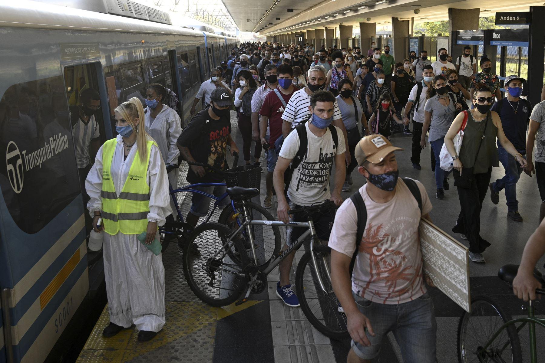 Una trabajadora espera para desinfectar la cabina de un tren de cercanías mientras los pasajeros descienden en la estación Once en Buenos Aires, el 7 de abril de 2021. Foto: AFP