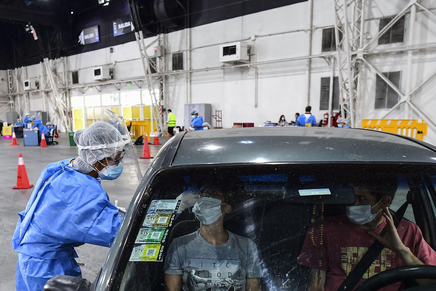 Un trabajador de salud recolecta muestras para la prueba de detección de casos de coronavirus dentro de un automóvil, en el centro de convenciones Costa Salguero, en Buenos Aires, el 5 de abril de 2021. Foto: AFP