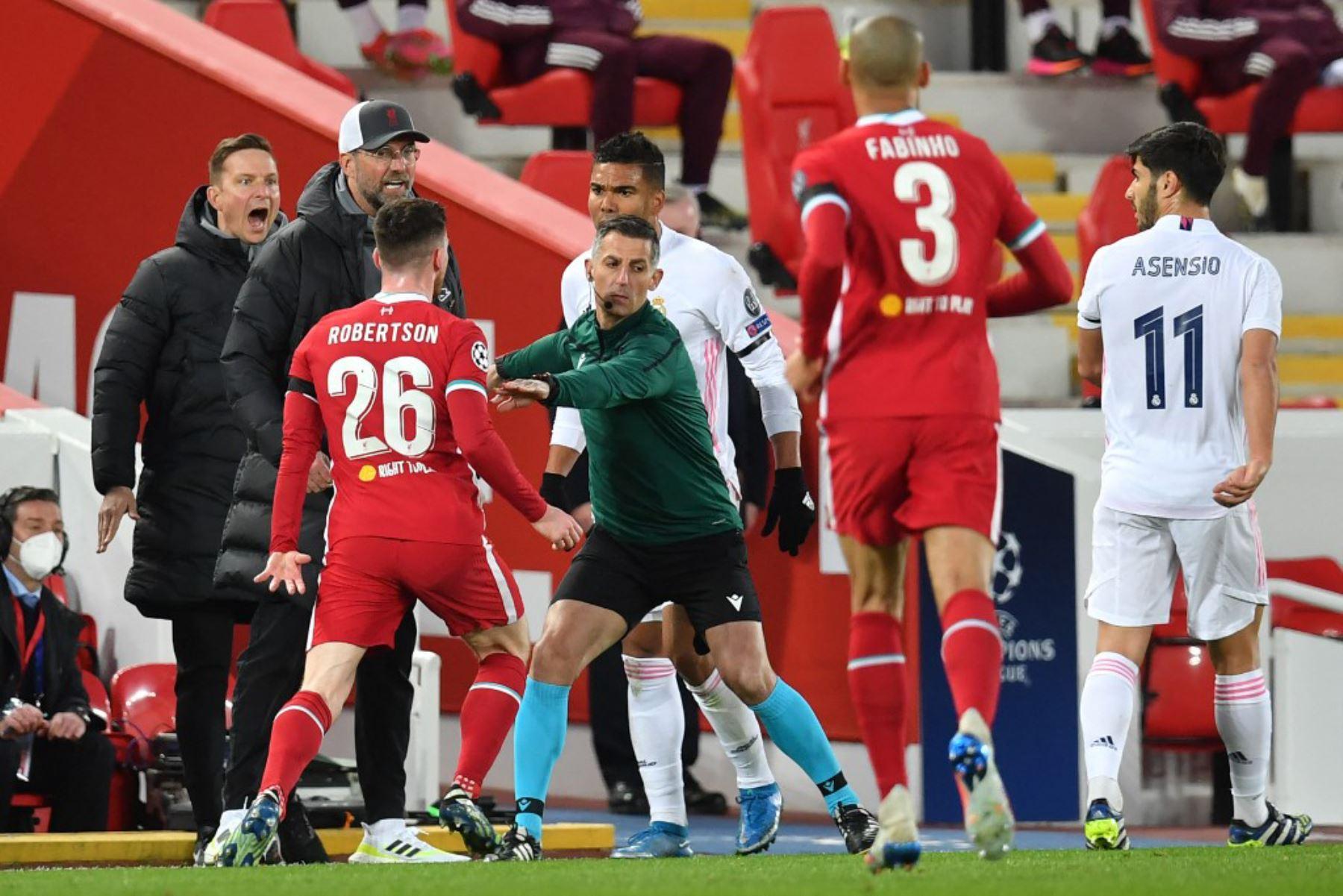 El árbitro Bjorn Kuipers (C) mantiene a raya al defensor escocés del Liverpool Andrew Robertson (L) durante un altercado durante los cuartos de final de la Liga de Campeones de la UEFA del segundo partido de fútbol entre el Liverpool y el Real Madrid en Anfield en Liverpool. Foto: AFP